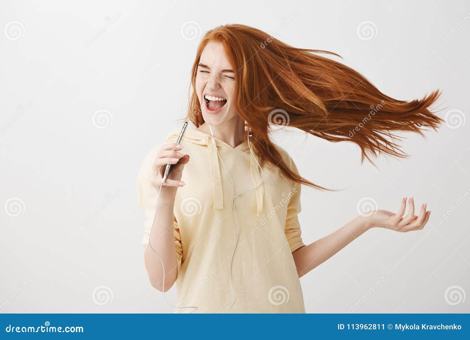 De muziek voert vertrouwen en geluk op Portret van gevoels charmante vrouw met rood haar die en het zingen lied dansen