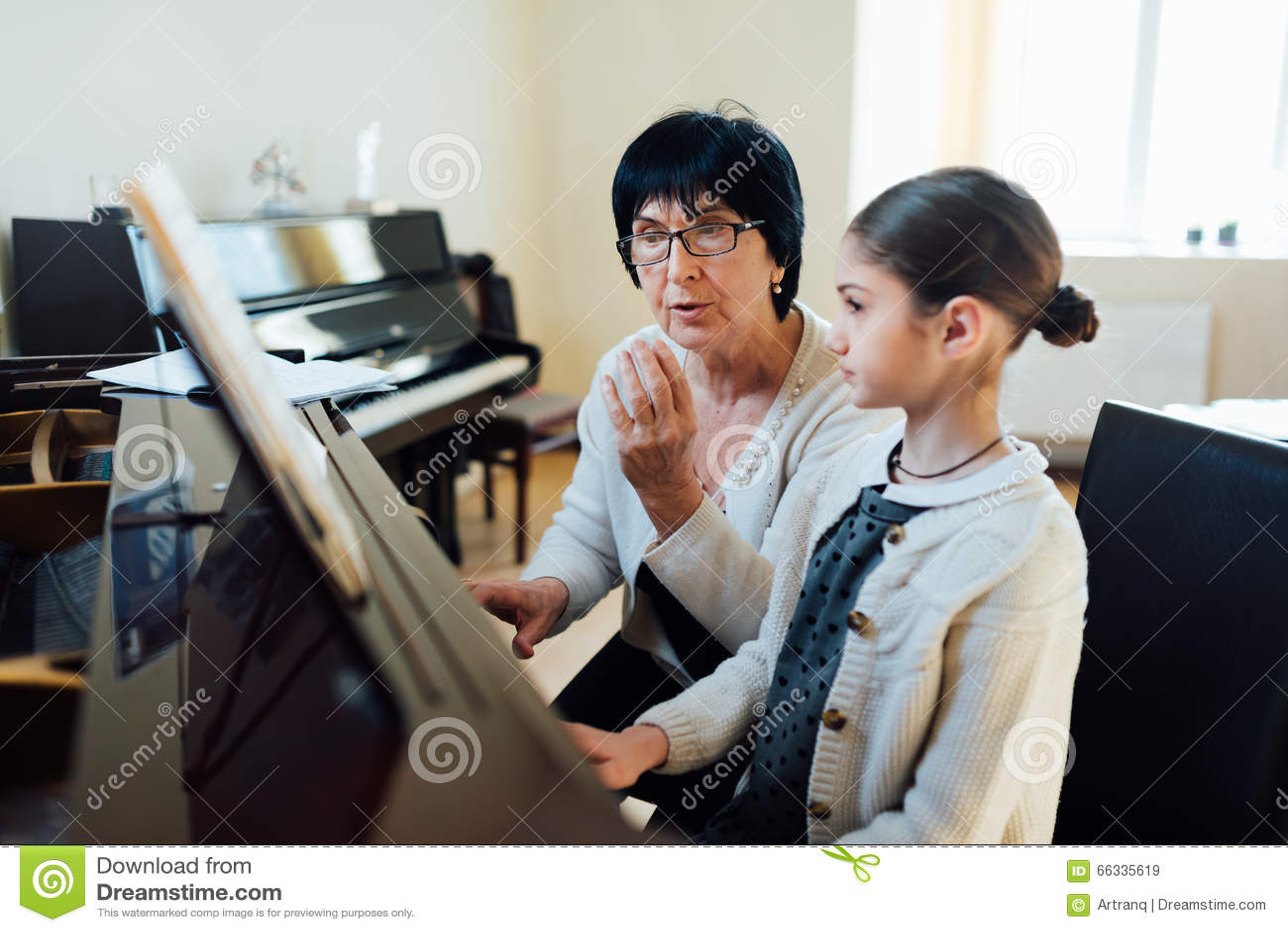 De muziekleraar verklaart ingewikkeldheden van het spelen piano