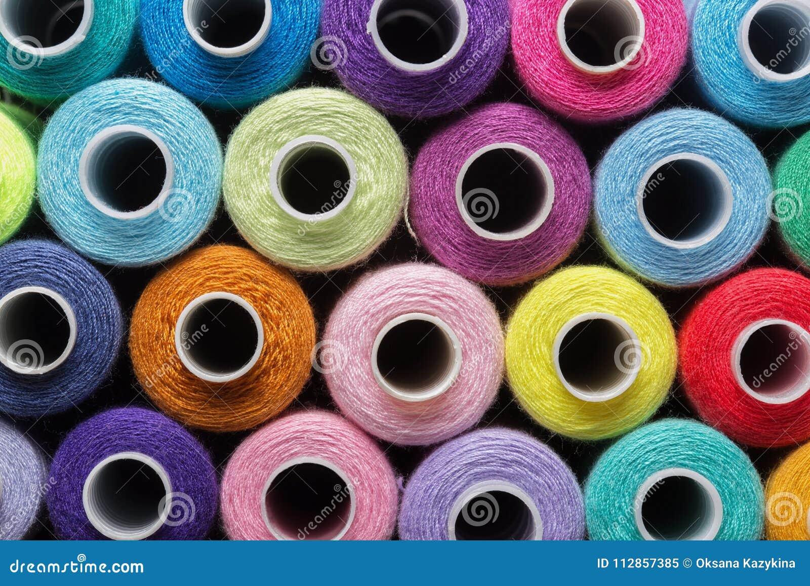 De naaiende draad in verschillende kleuren doorboort blauwgroen rood