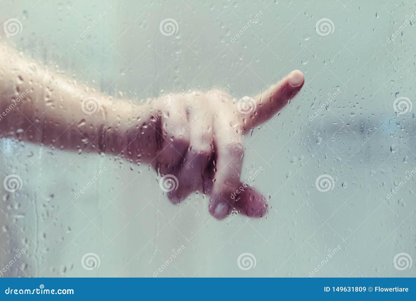 De naakte mooie vrouw een douche nemen en de aanrakingen die overhandigen nat misted glas