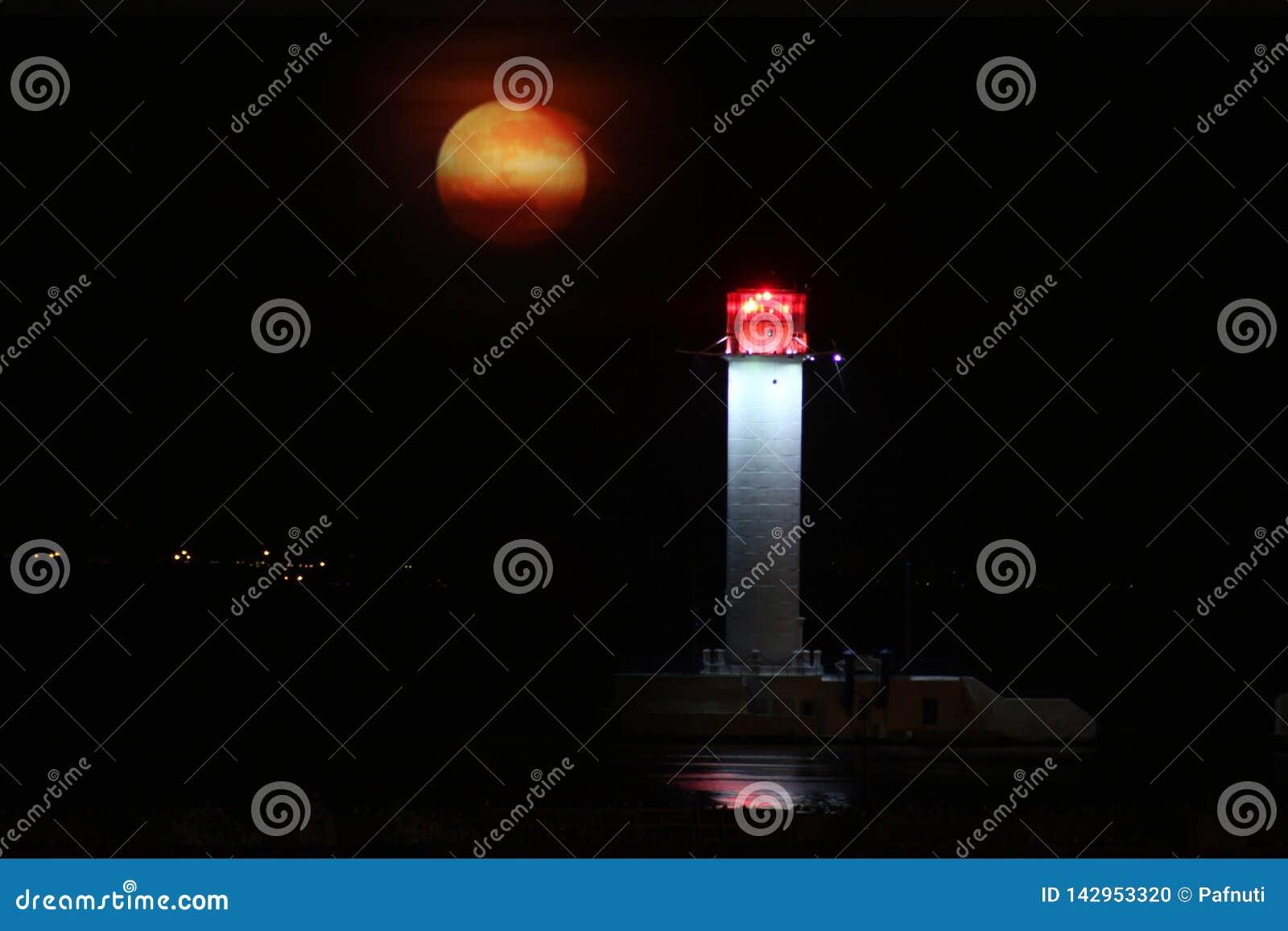 De nacht van de Vorontsovvuurtoren tegen het toenemen van de grote rode maan