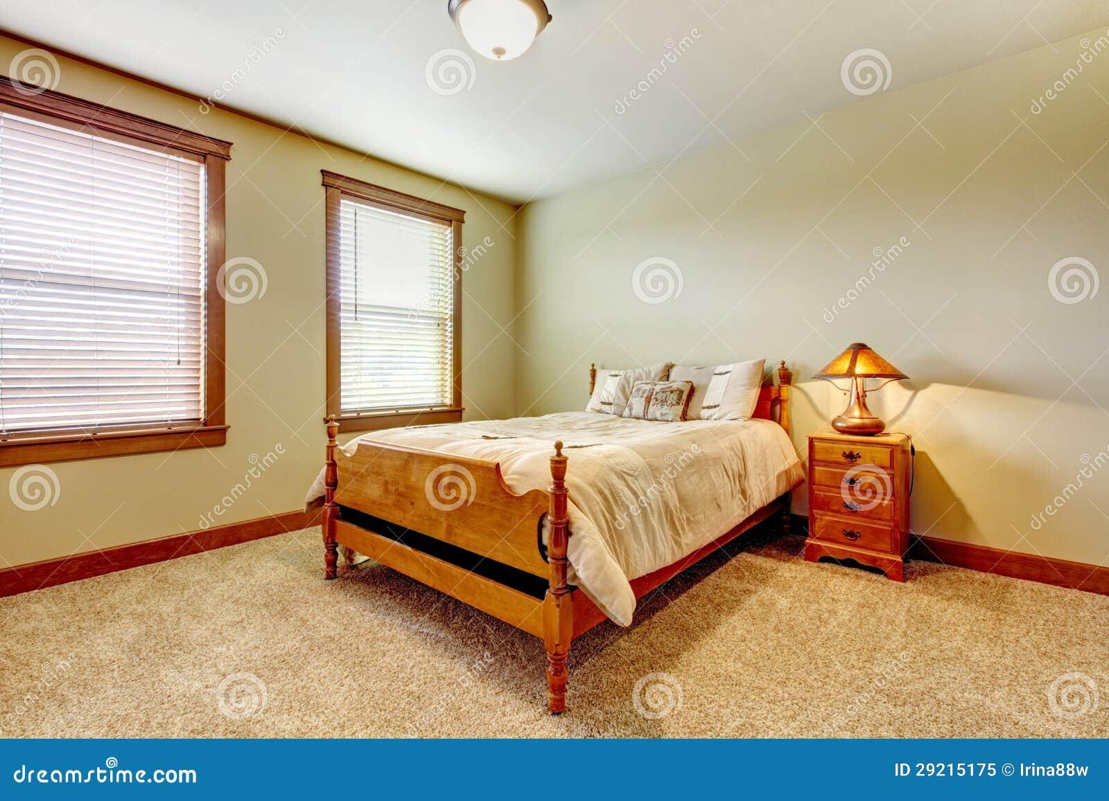 De natuurlijke slaapkamer van het landbouwbedrijfhuis met beige tapijt ...