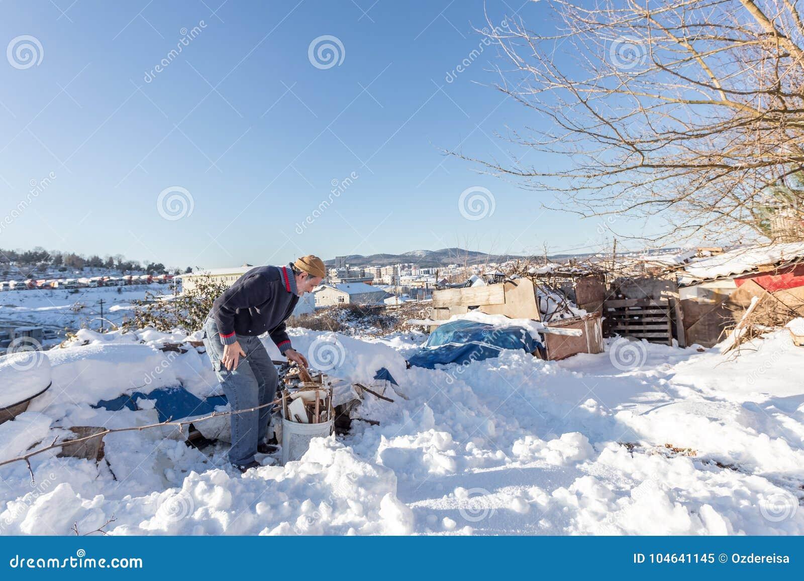 De niet geïdentificeerde oude Turkse mens zet gehakt brandhout in een plastic emmer