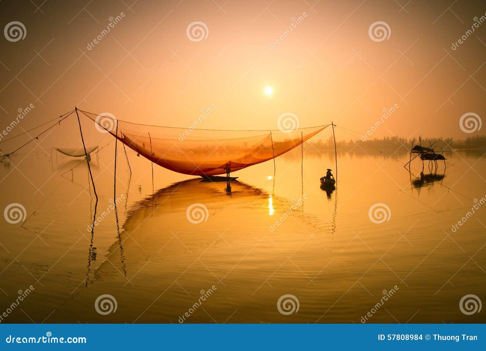 De niet geïdentificeerde visser controleert zijn netten in vroege ochtend op rivier in Hoian, Vietnam