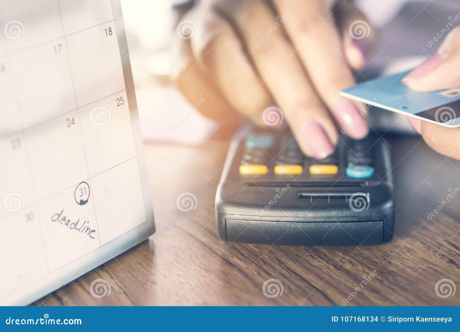 De nota van de uiterste termijnkalender met onduidelijk beeldachtergrond van bedrijfsvrouwenhand die haar schuld op calculator me