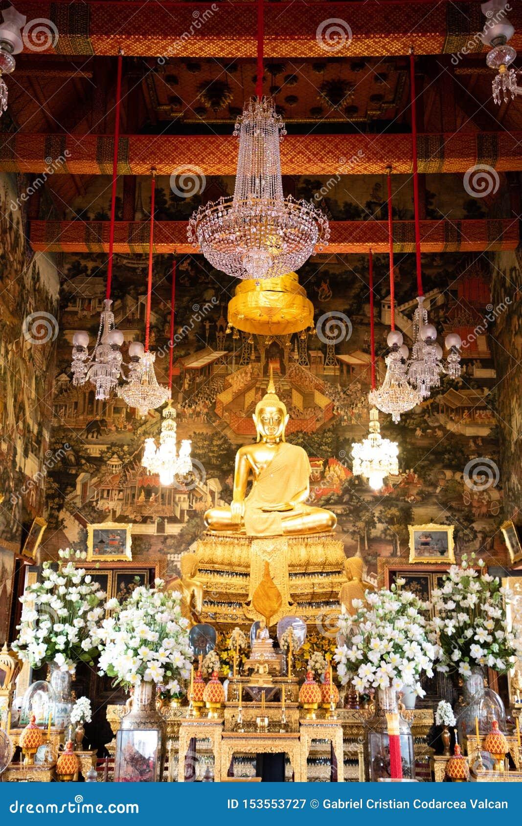 20 de novembro de 2018 - Banguecoque TAILÂNDIA - Buda dourada grande cercada pelas orquídeas brancas no templo tailandês