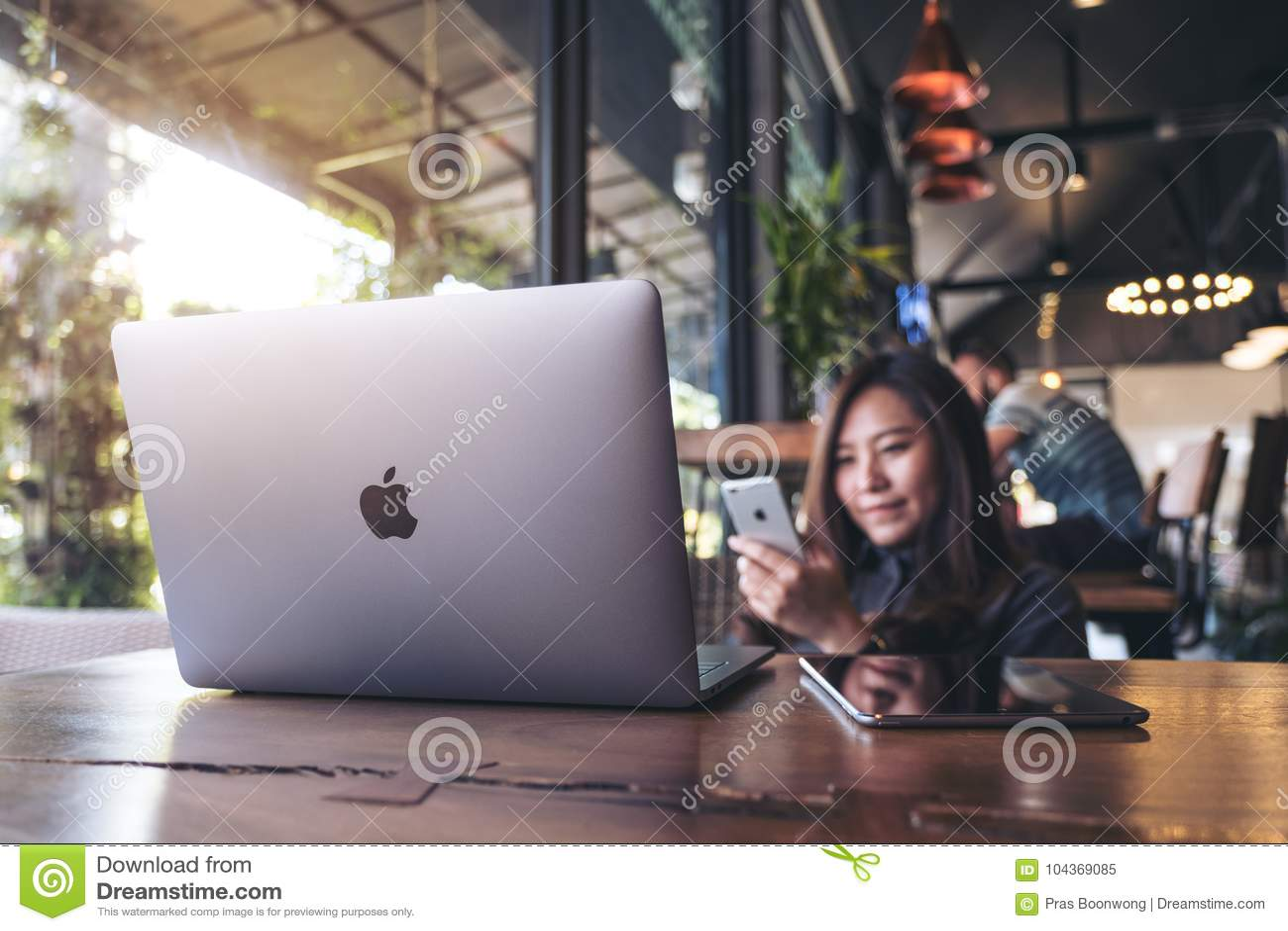 17 de noviembre de 2017: Mujer de negocios asiática que sostiene el teléfono elegante con el ordenador portátil en la tabla de ma