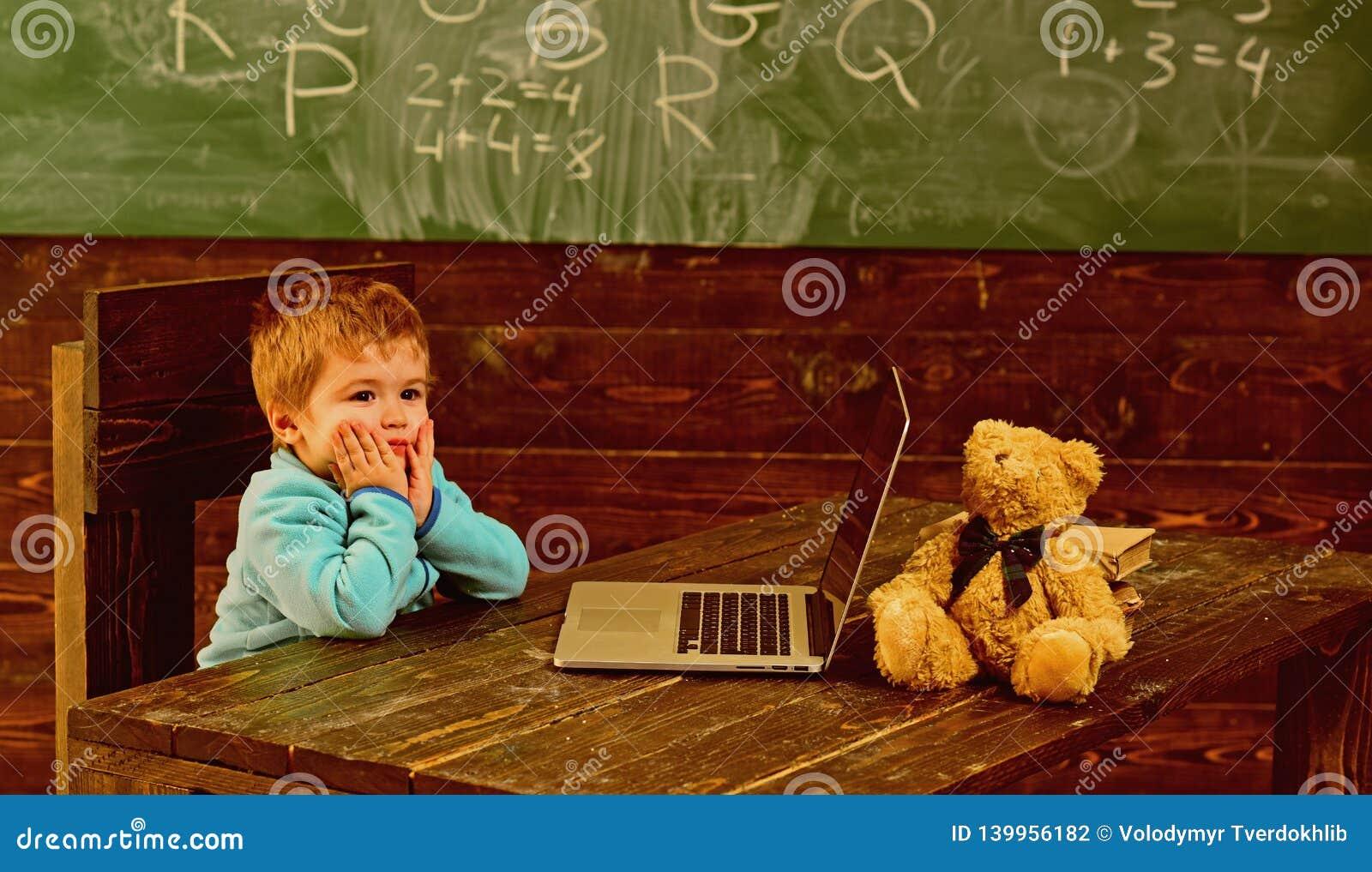 De nuevo a escuela El niño pequeño está de nuevo a escuela De nuevo a escuela con nueva tecnología De nuevo a escuela y a parecer