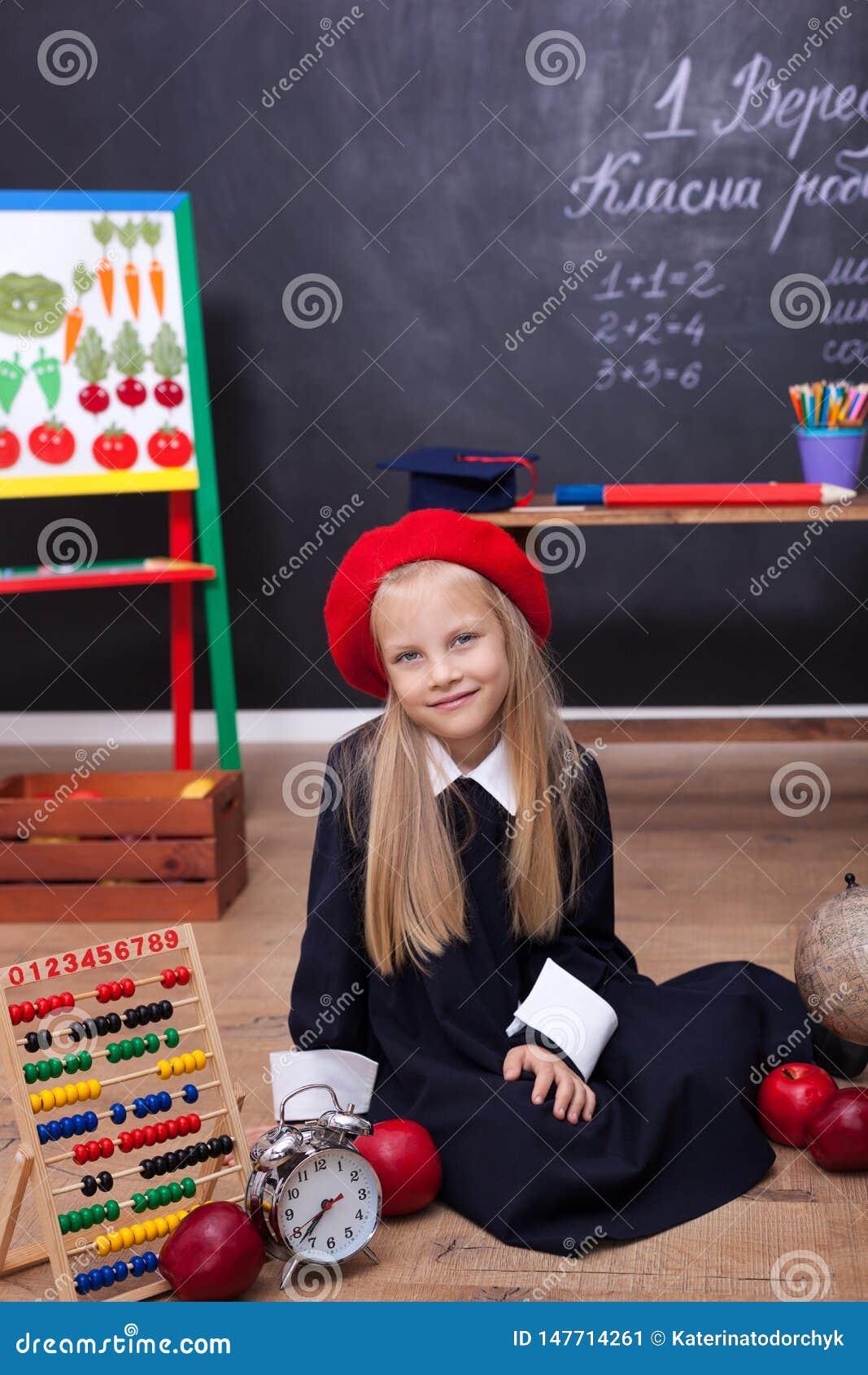 ?De nuevo a escuela! Una muchacha en el uniforme escolar que se sienta en una lecci?n Responde a la lecci?n En la pizarra en la l