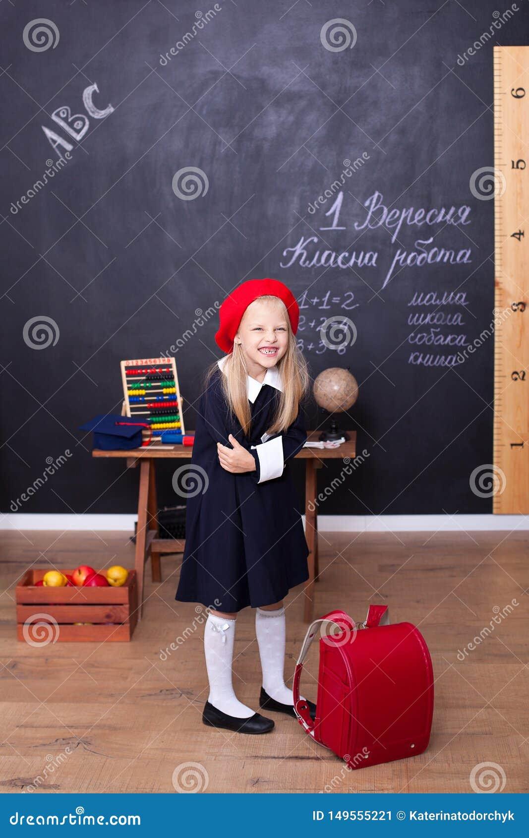 ?De nuevo a escuela! Una muchacha se coloca en escuela con una mochila roja Responde a la lecci?n Concepto de la escuela En la pi