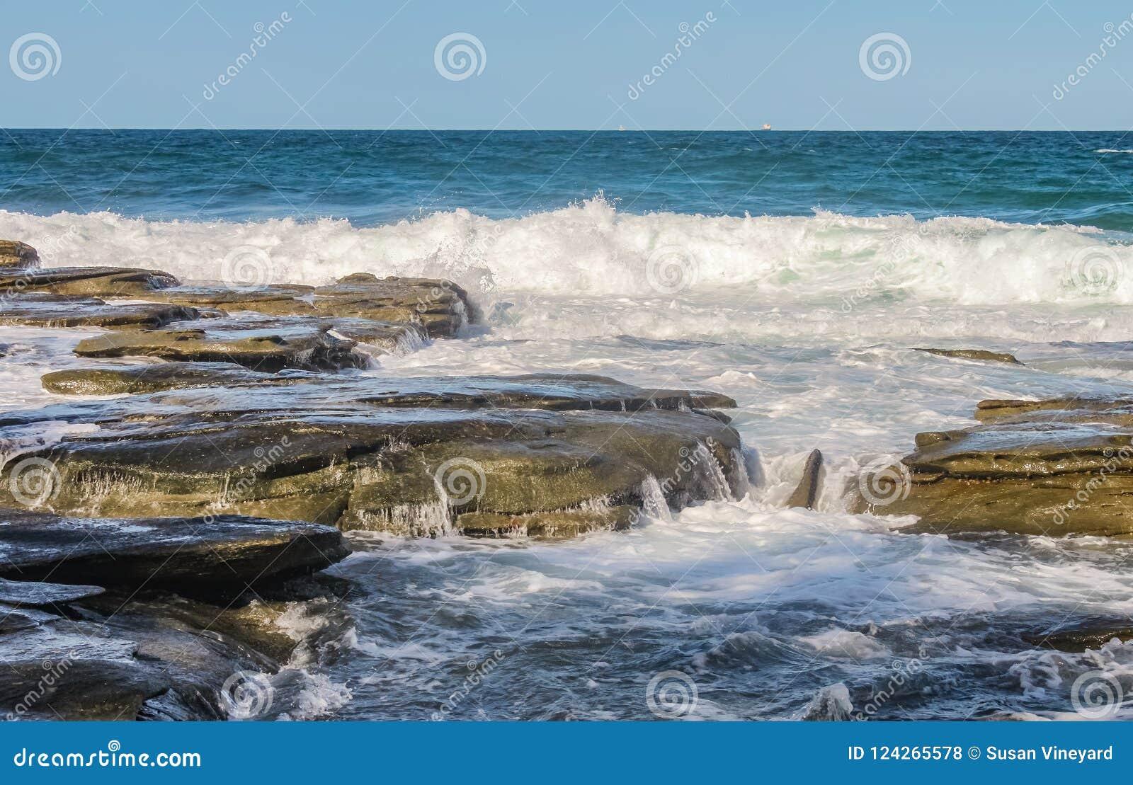 De oceaangolven verpletteren tegen eeuwigheden oude vulkanische rots en waterlooppas en onderbrekingen de steen - met uiterst kle