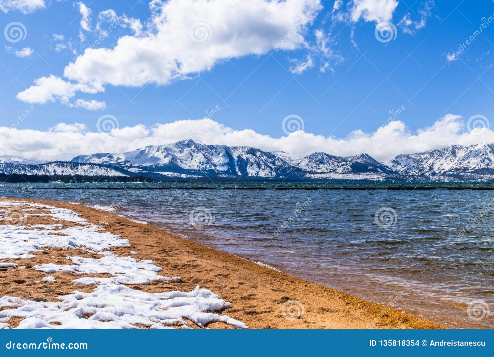 De oever en de sneeuw van Tahoe van het zuidenmeer behandelden zandig strand, op een zonnige dag; de sneeuw behandelde Siërra ber