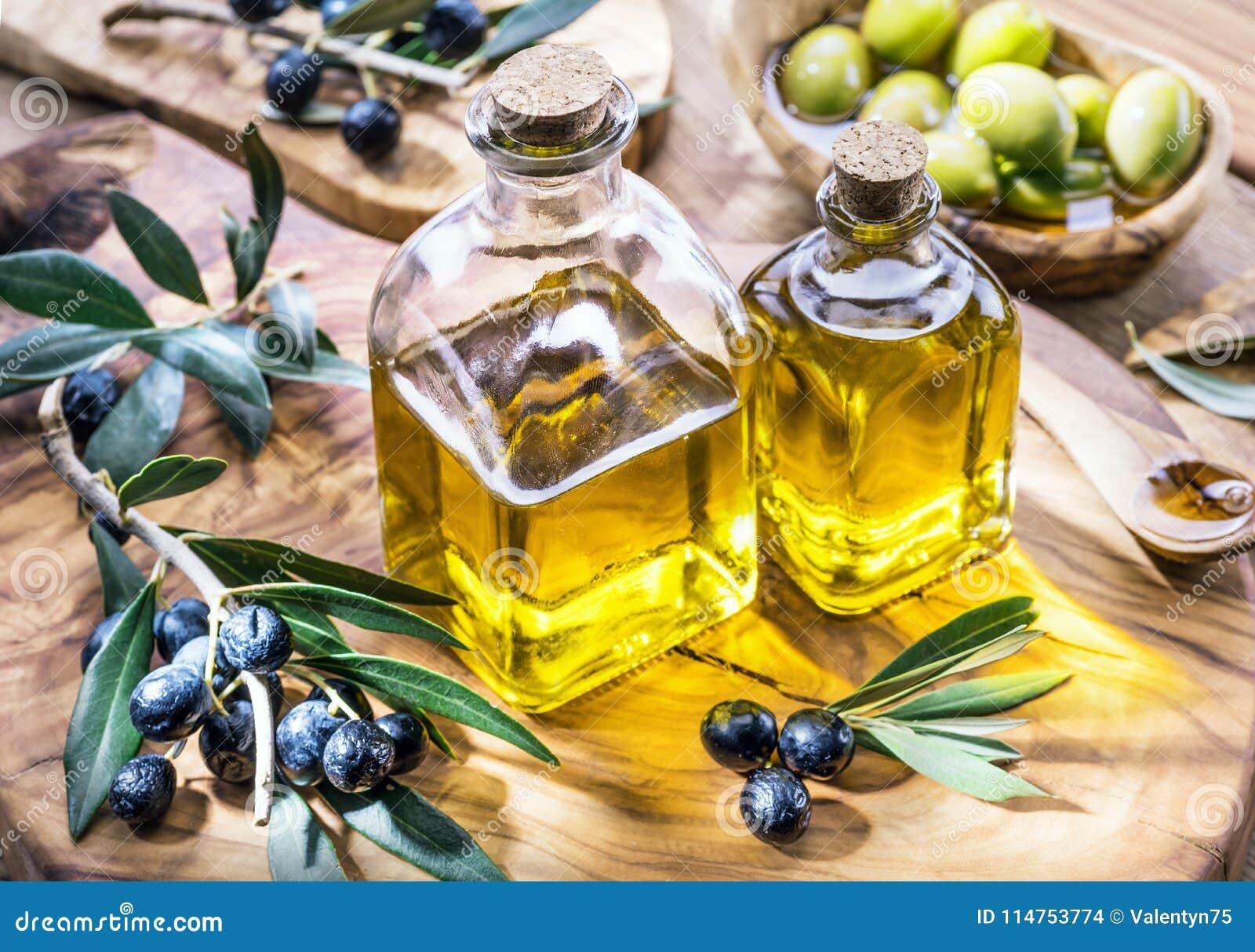 De olijfolie en de bessen zijn op het olijf houten dienblad