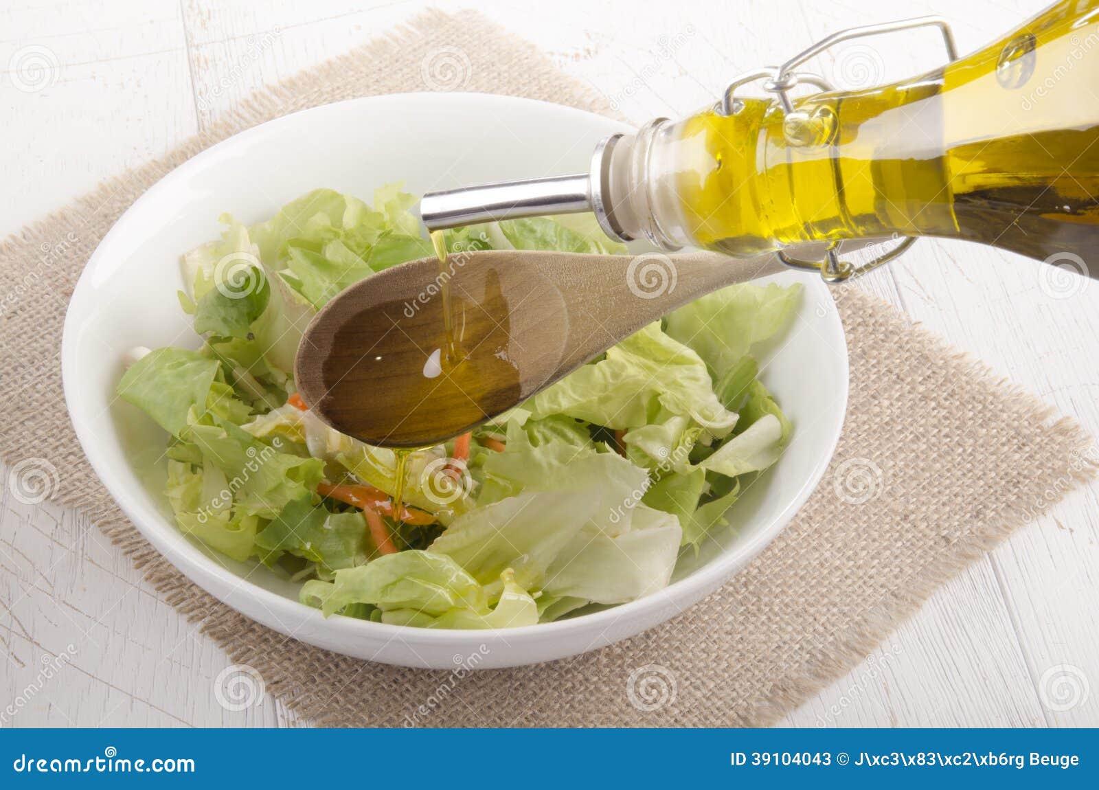 De olijfolie wordt gegoten in een saladekom