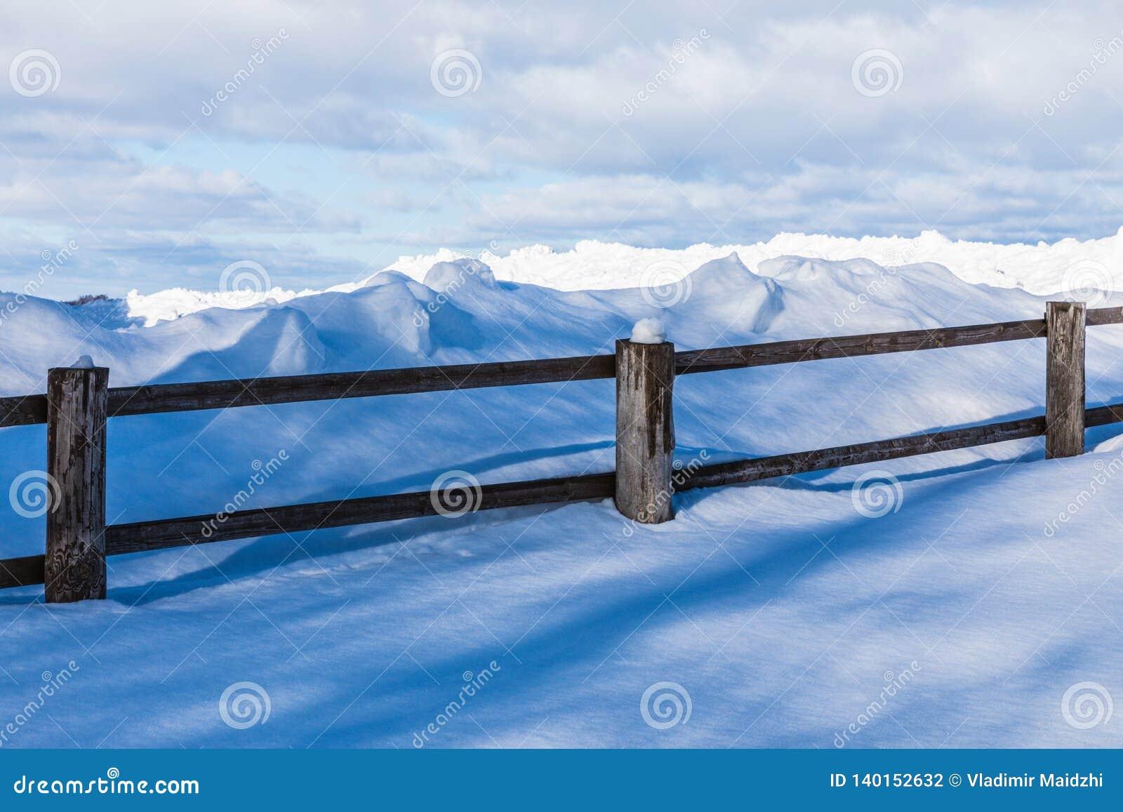 De omheining of de haag en de hopen van sneeuw in het platteland of in het dorp in de koude de winterdag