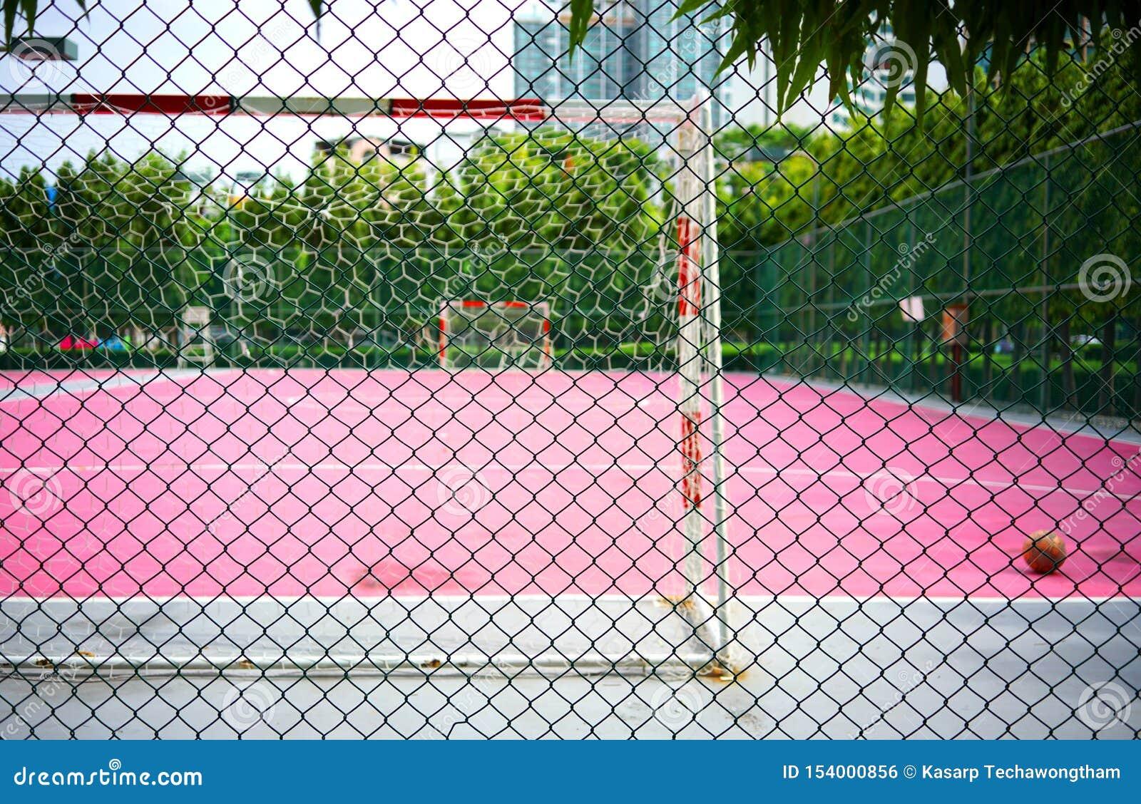 De omheining van de metaaldraad of van het draadnetwerk groen staal met onduidelijk beeldvoetbal of roze Futsal-Sporten die achte