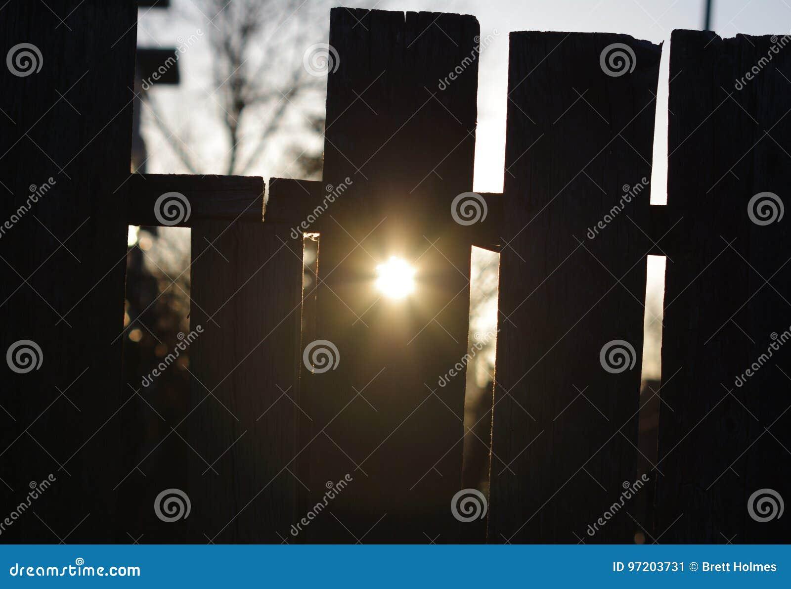 De onderbrekingen van de ochtendzon door een gat in omheining