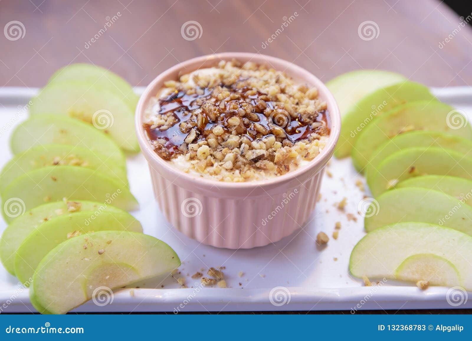 De Onderdompeling van karamelapple met noten, karamelvulling en verse appelplakken