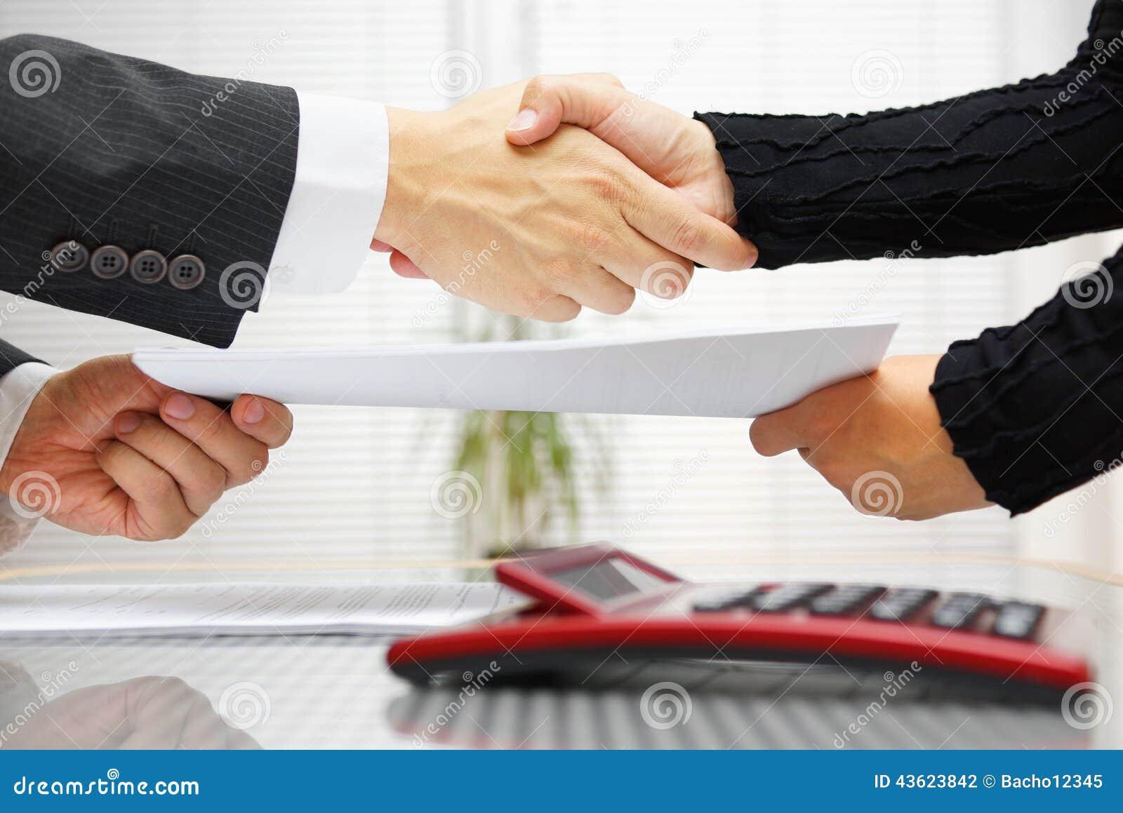 De onderneemster en de zakenman zijn handenschudden en ruilend bedrieg