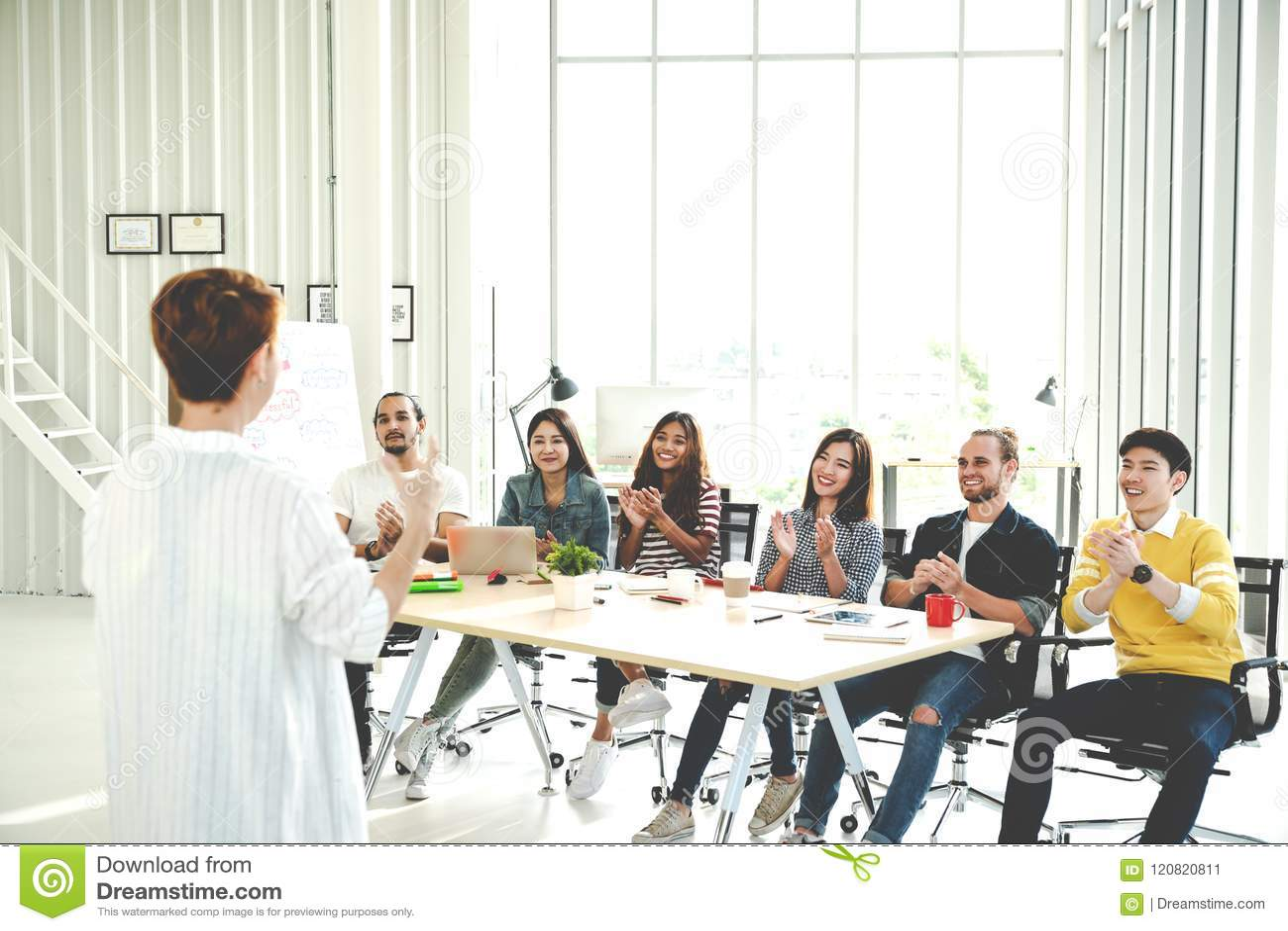 De onderneemster verklaart ideeën zich van creatief divers team op modern kantoor te groeperen Achtermening van manager gesturing