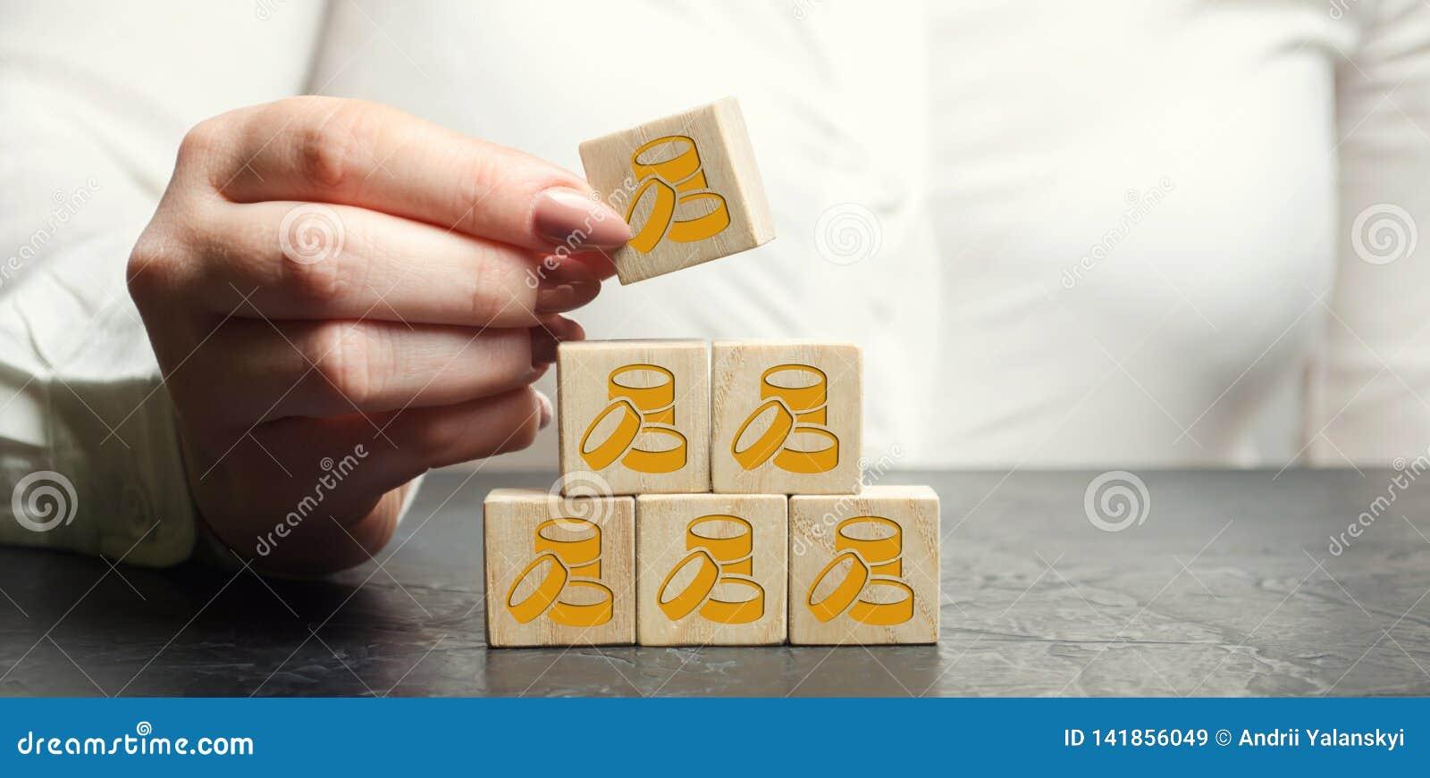 De onderneemster zet of verwijdert houten blokken met muntstukken Het concept het accumuleren van winsten Financiële Growth Succe