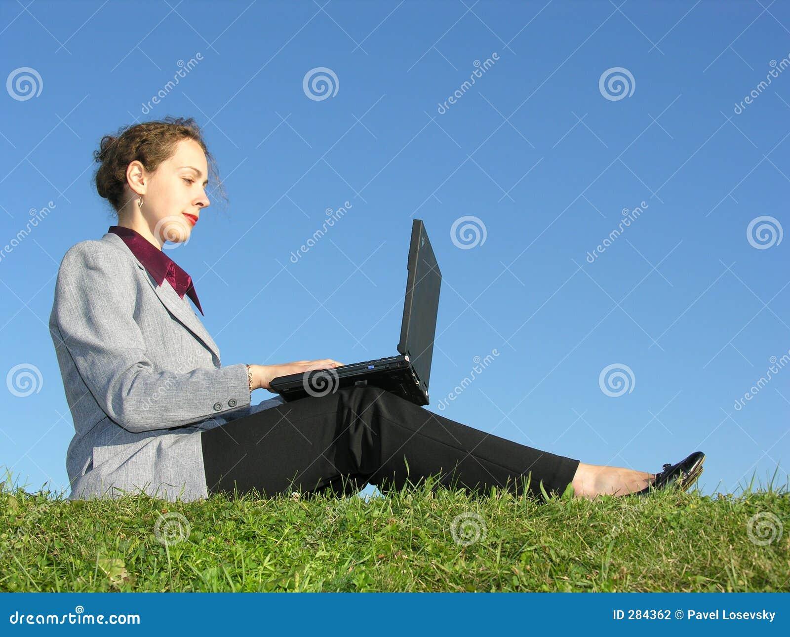 De onderneemster zit met notitieboekje op blauwe hemel