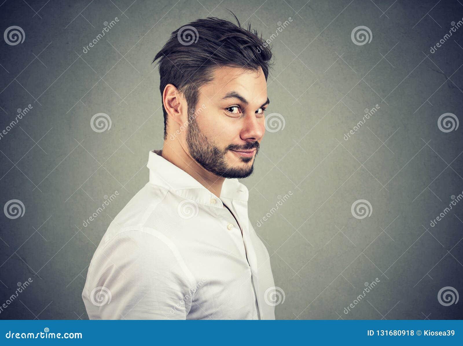 De oneerlijke mens die in wit overhemd kijken met beweert glimlach bij camera op grijze achtergrond