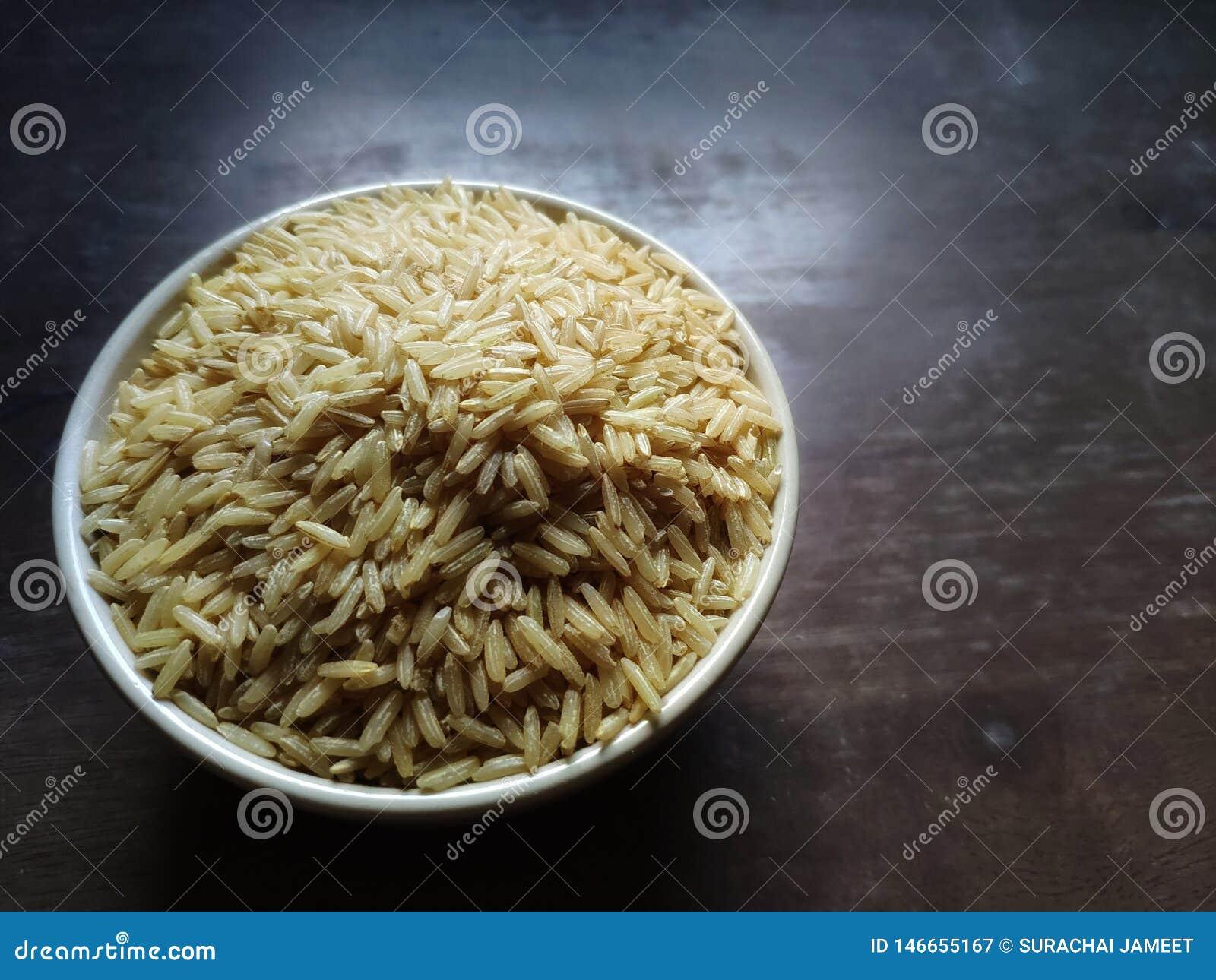 De ongepelde rijst wordt geplaatst in een witte kom op een houten lijst