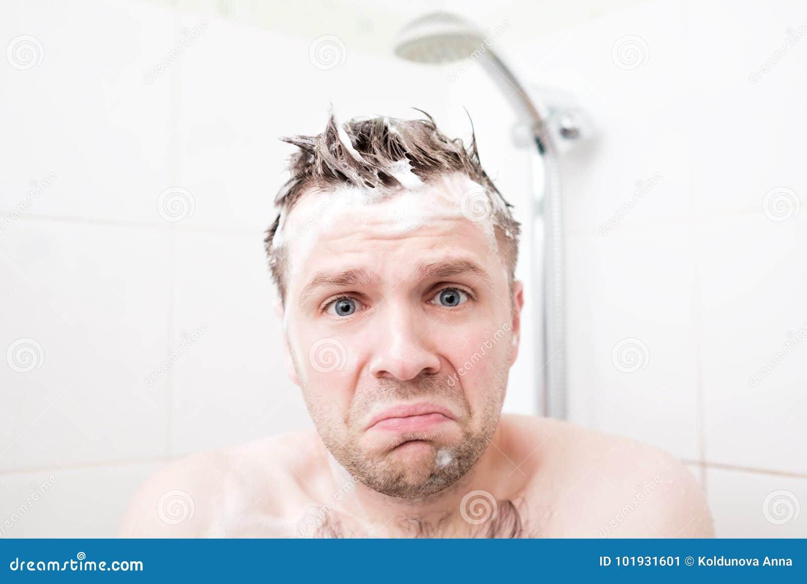 De ongerust gemaakte schuim jonge mens na het water in de douche werd uitgezet, bekijkend de camera