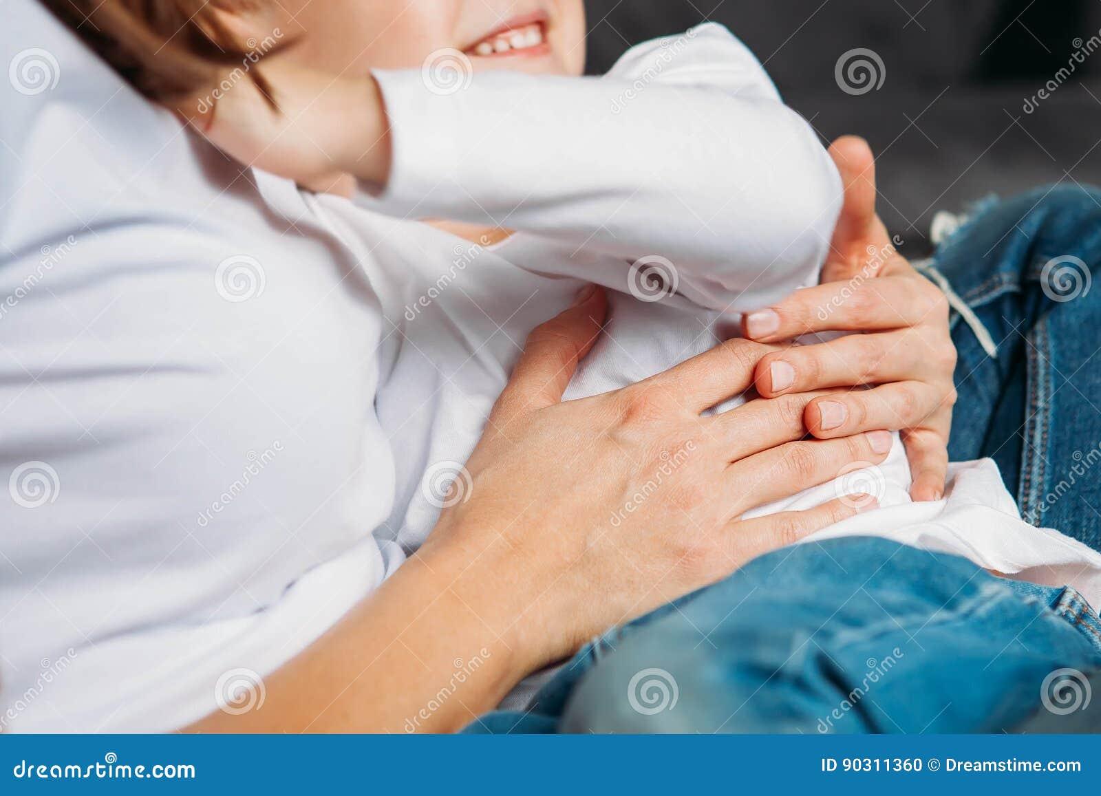 De onherkenbare zoon van de moederholding in haar wapens sluit omhoog handen