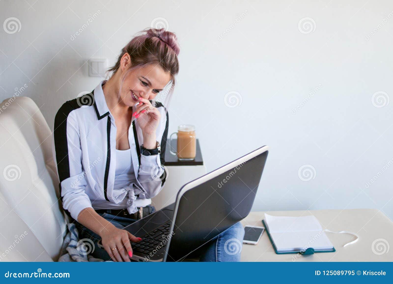 De online mededeling, een jonge vrouw bekijkt laptop en lacht