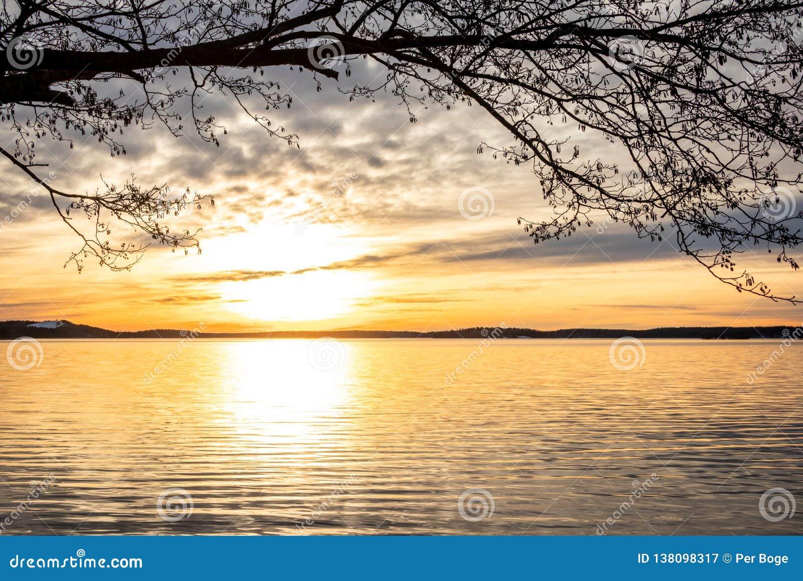 De ontworpen mooie oranje zonsondergang van het de winterlandschap over kalm meerwater met heldere zon tegen overzeese horizon