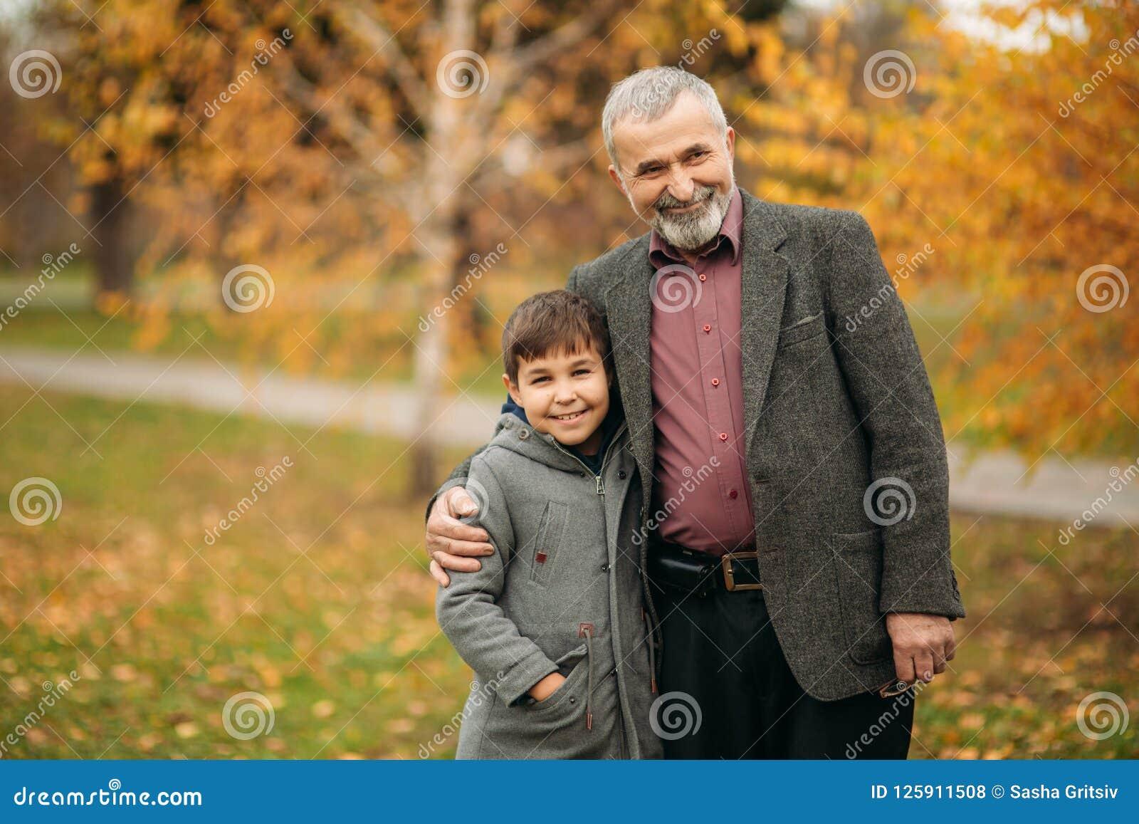 De opa en zijn kleinzoon lopen in het park Breng samen tijd door