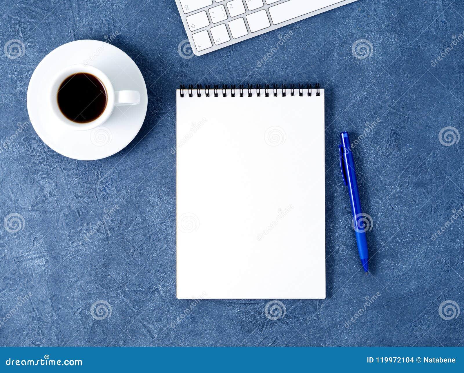 De open blocnote met schone witte pagina, de pen en de koffie vormen op oude donkerblauwe steenlijst tot een kom, hoogste mening