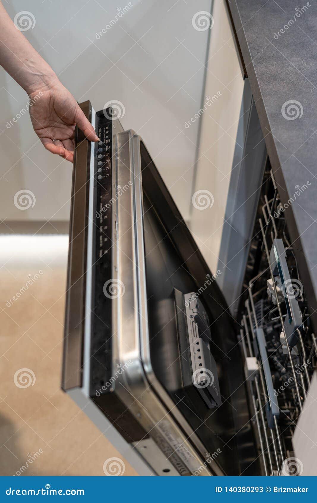 De openingsdeur van de vrouwenhand in nieuwe moderne ingebouwde afwasmachine