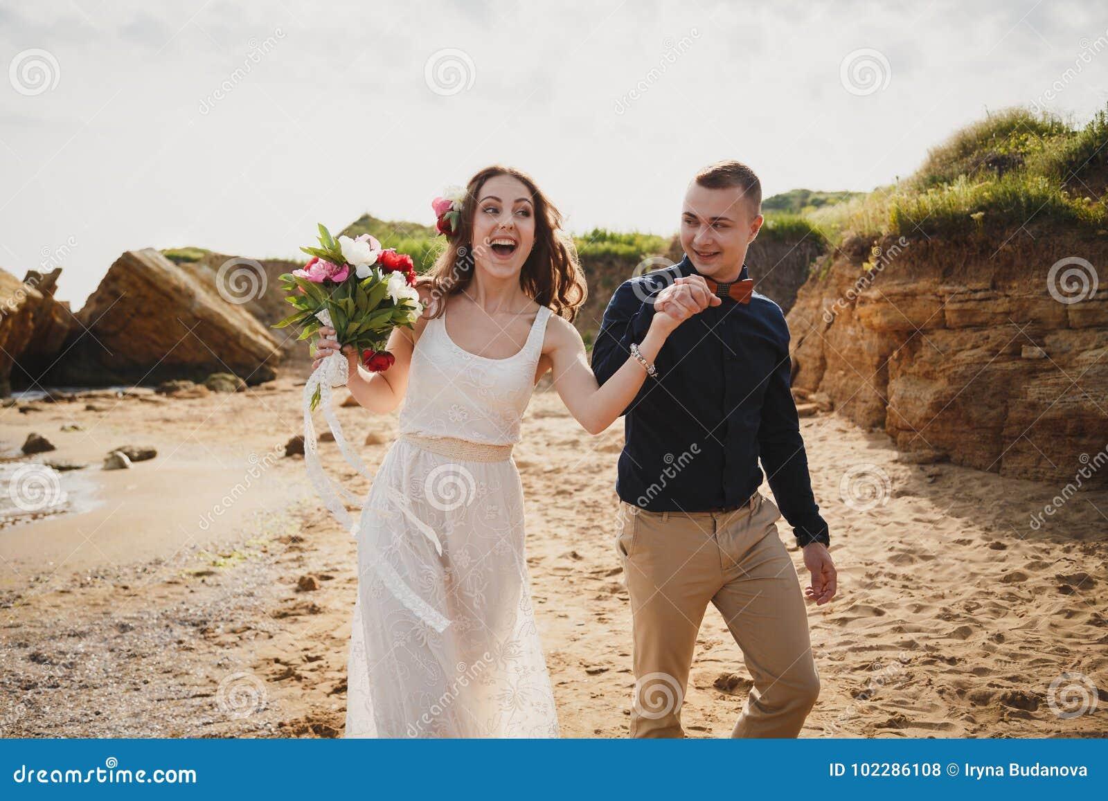 De openluchtceremonie van het strandhuwelijk dichtbij het overzees, de modieuze gelukkige glimlachende bruidegom en de bruid hebb