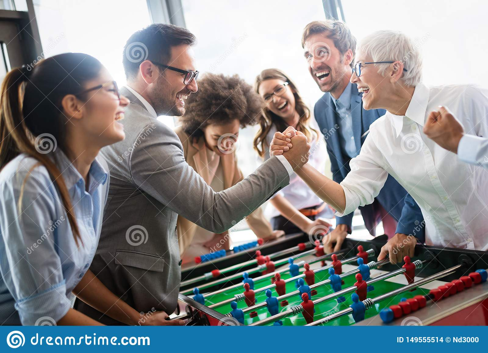 De opgewekte diverse werknemers die van grappige activiteit genieten bij het werkonderbreking, creatieve vriendschappelijke arbei