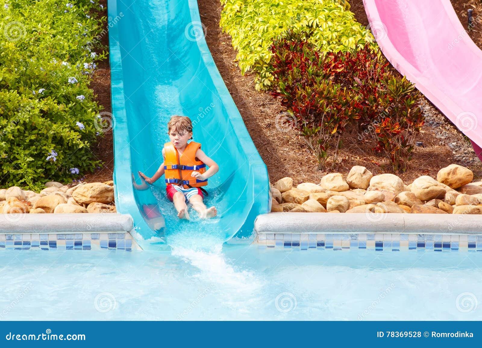 De opgewekte kinderen in water parkeren het berijden op dia met vlotter