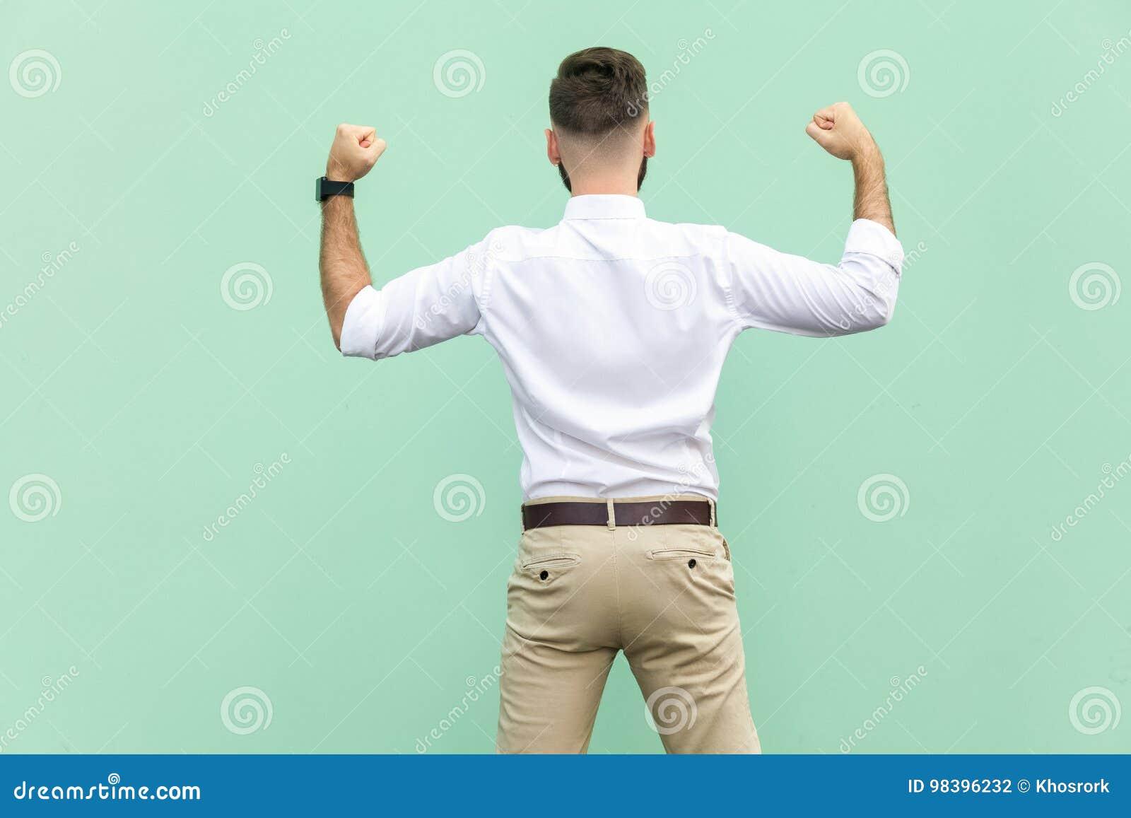 De opgewekte zakenman viert een carrièrevoltooiing Achtermening van een jonge volwassen zakenman, op lichtgroene achtergrond