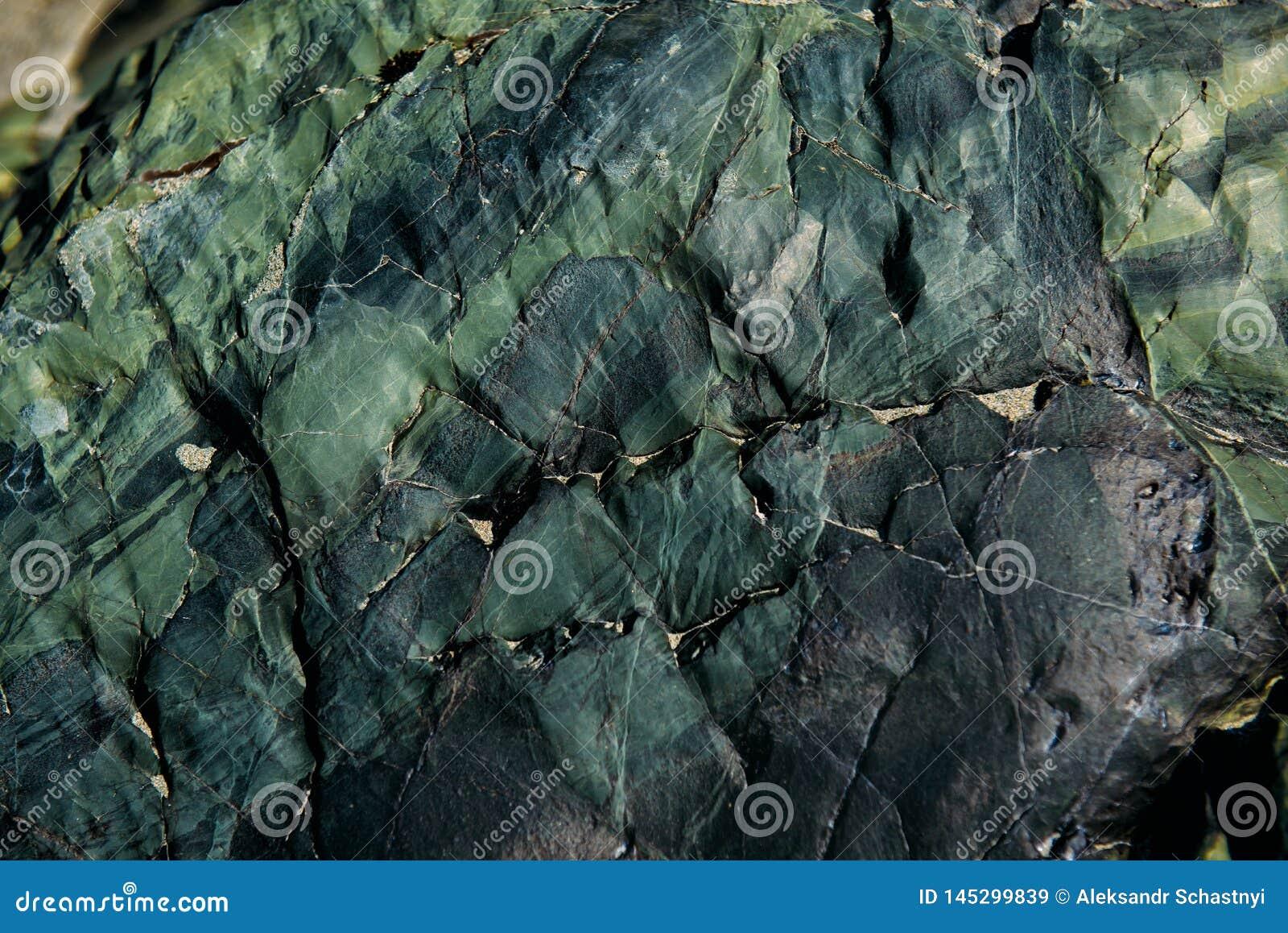 De oppervlakte van een oude rots met barsten De oude wilde achtergrond van de rotstextuur