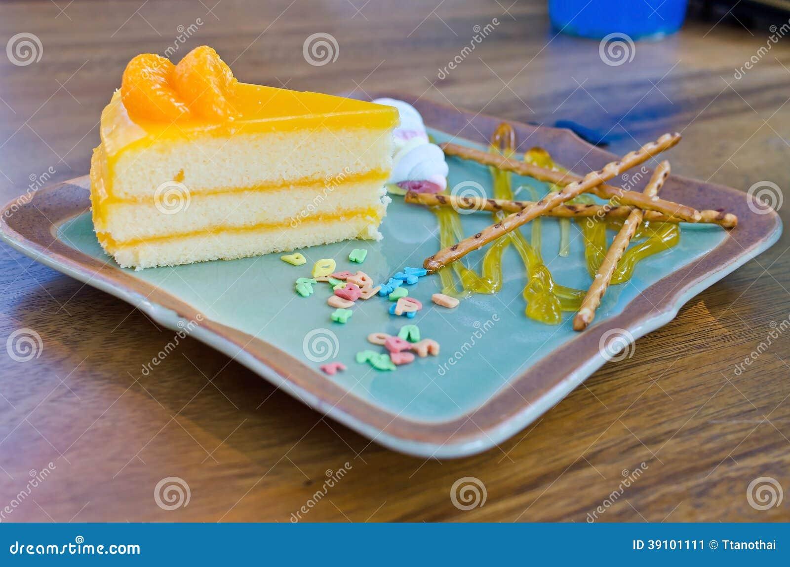 De oranje cake met Kleurrijk suikergoed bestrooit op plaat