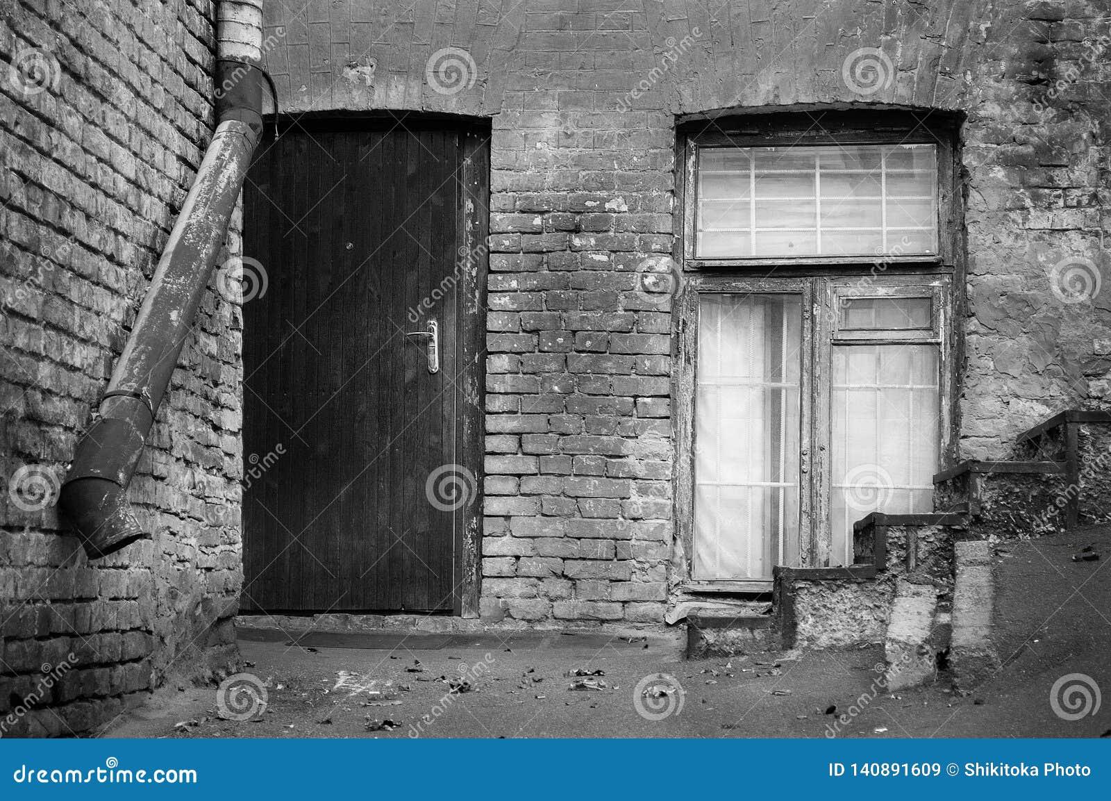 De oude baksteenbouw met houten deur en venster