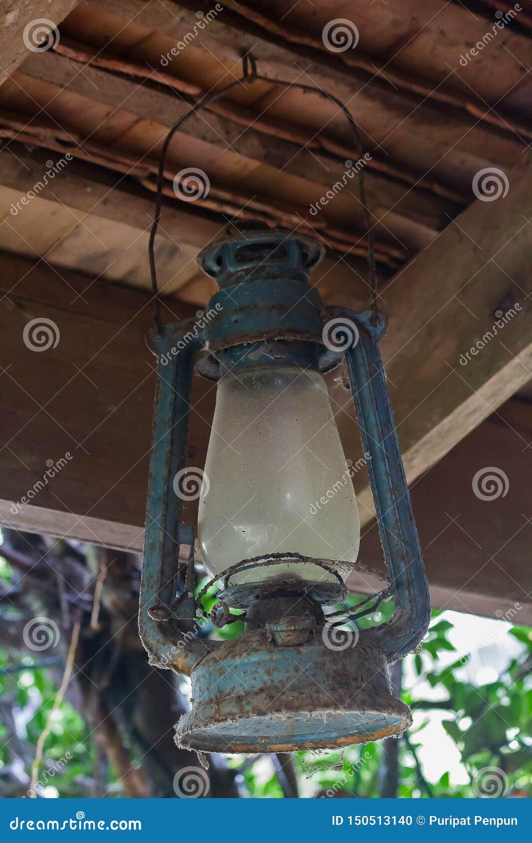De oude blauwe orkaanlamp hing op de straal