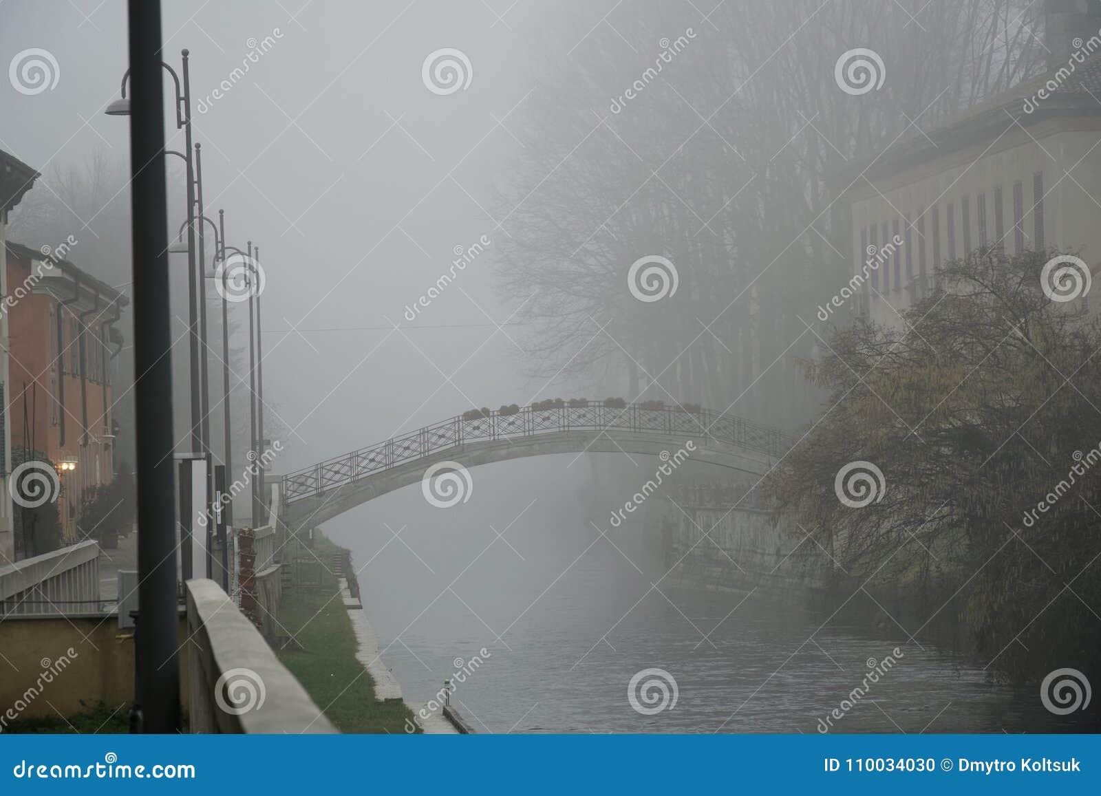 De oude brug van de Boogsteen in mistig weer, de nevelwinter in Italië