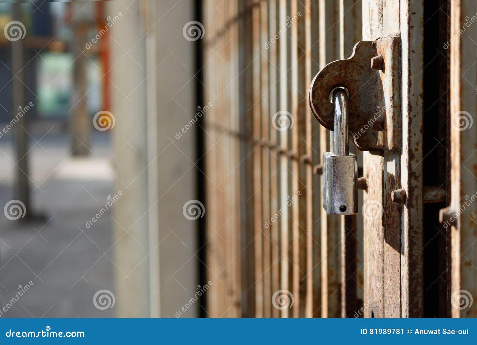 De oude deur van het roestmetaal die met zilveren hangslot wordt gesloten
