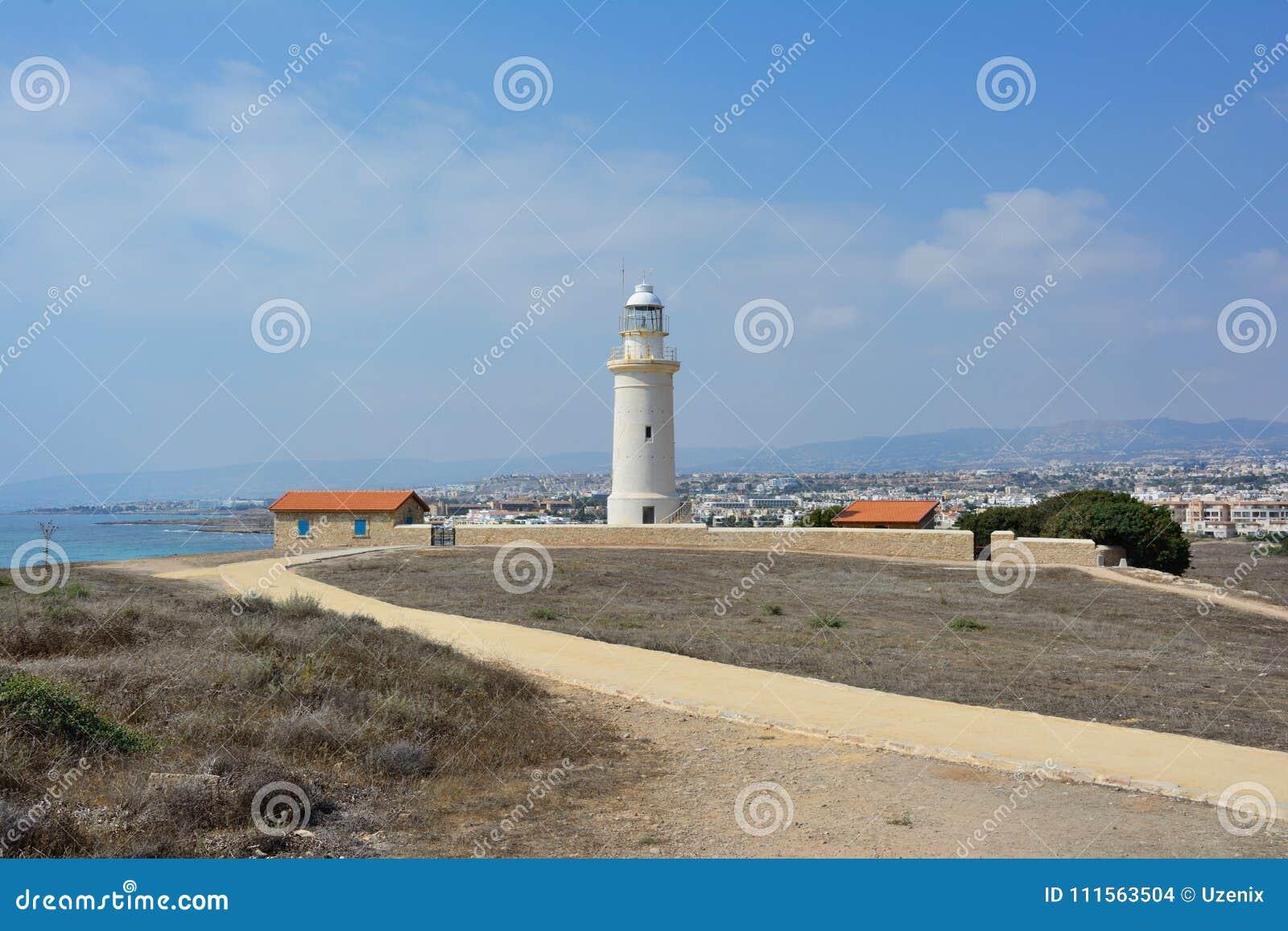 De oude die vuurtoren op de achtergrond van de stad van Paphos op het Eiland Cyprus in de Middellandse Zee wordt gevestigd