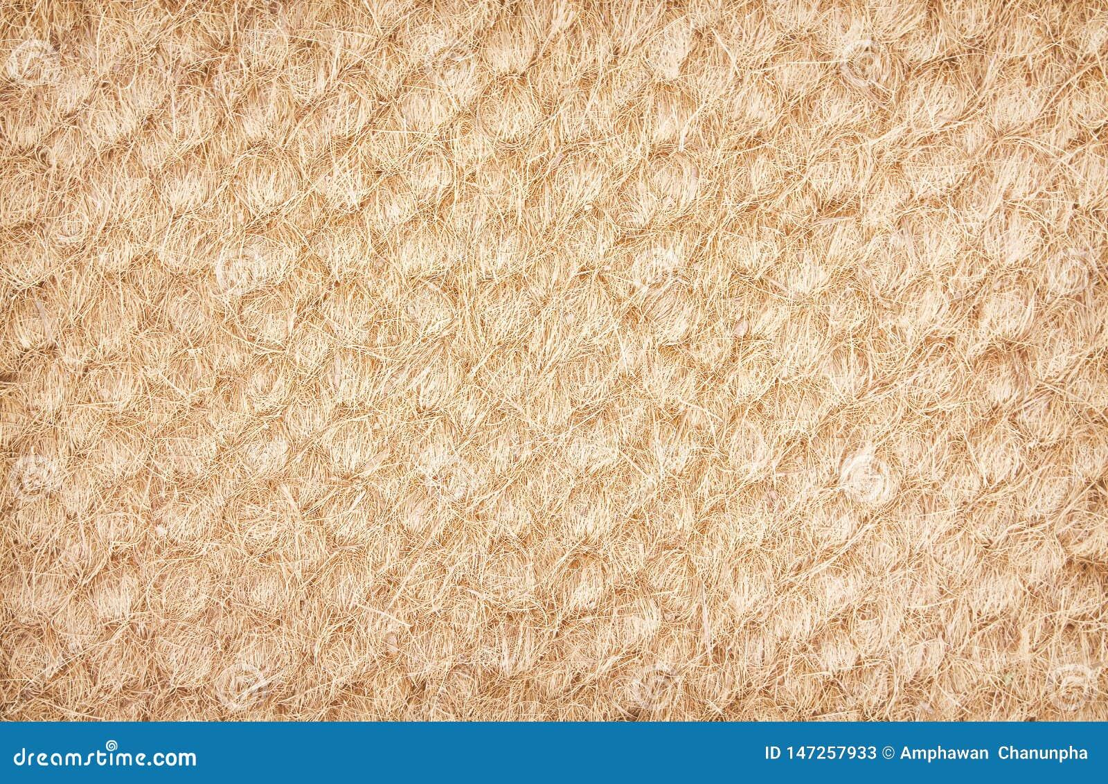 De oude droge textuur van de kokosvezeldeurmat, de achtergrond van aardpatronen