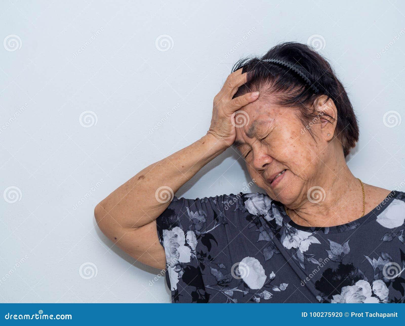 De oude hogere vrouw die en aan gezicht lijden behandelen met dient hoofdpijn en diepe depressie in emotionele wanorde, zorg en w