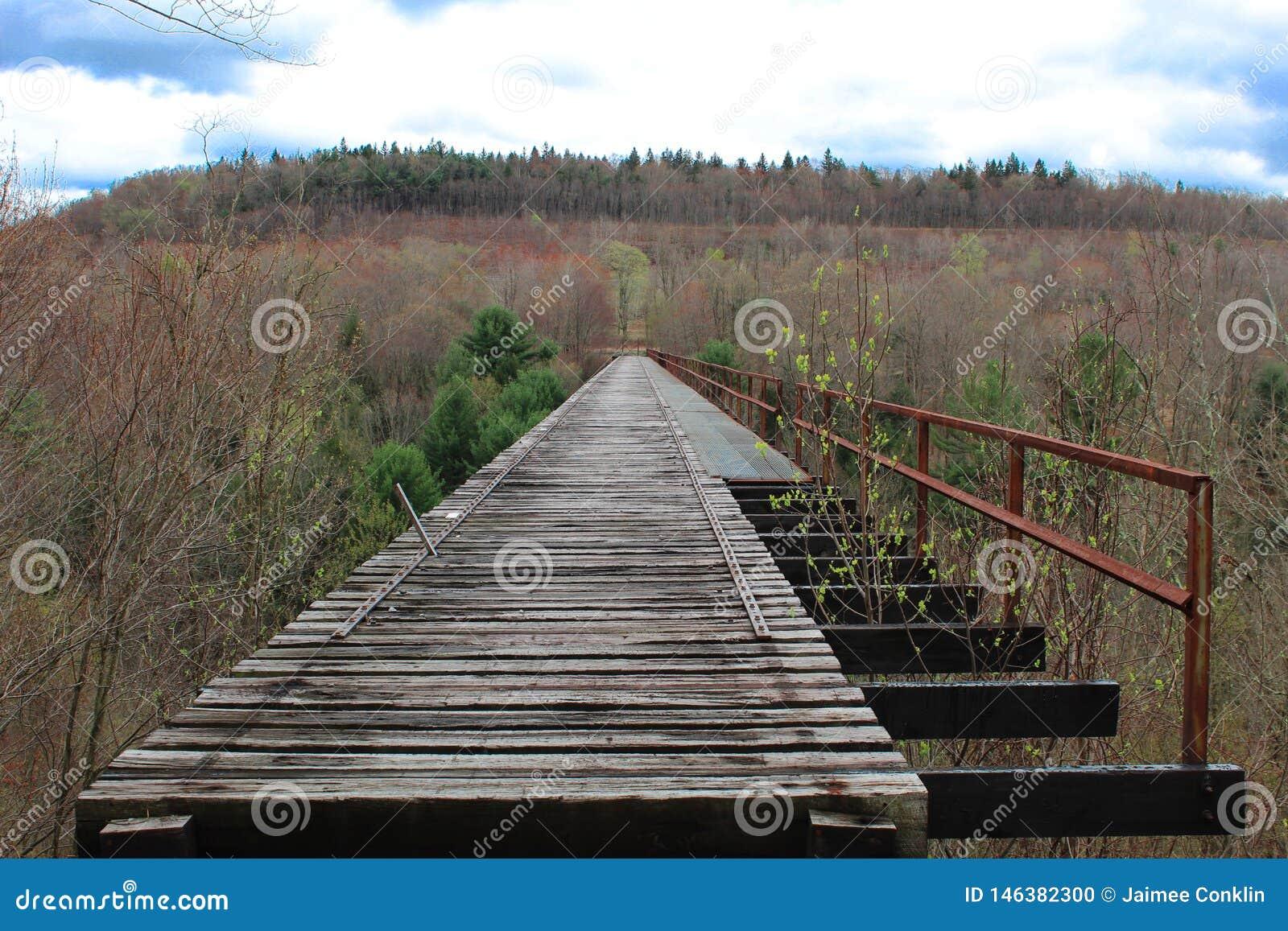 De oude houten brug van de viaducttrein met roestig spoor