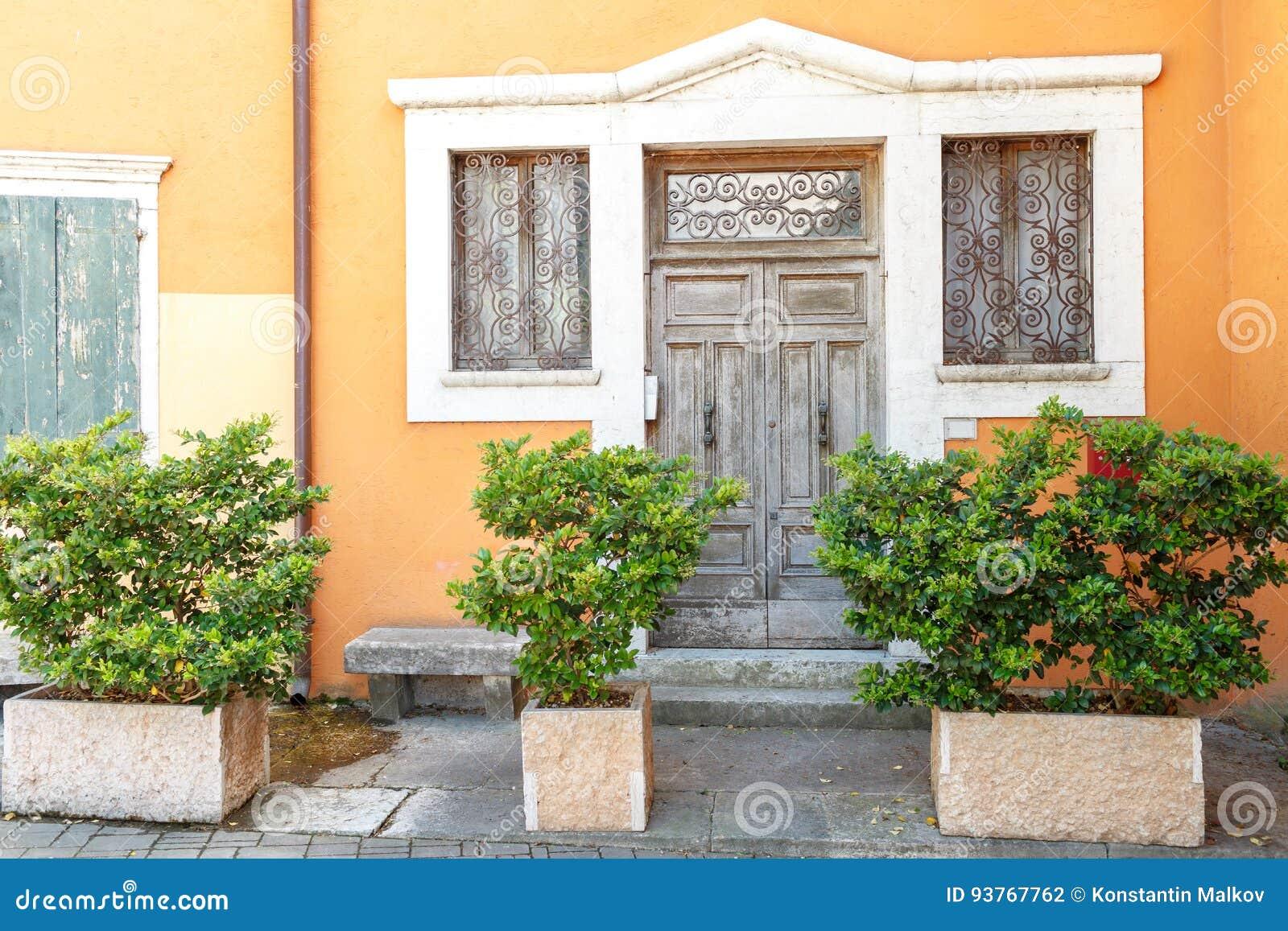 De oude ingangsdeur en het venster met blinden in de muur van een